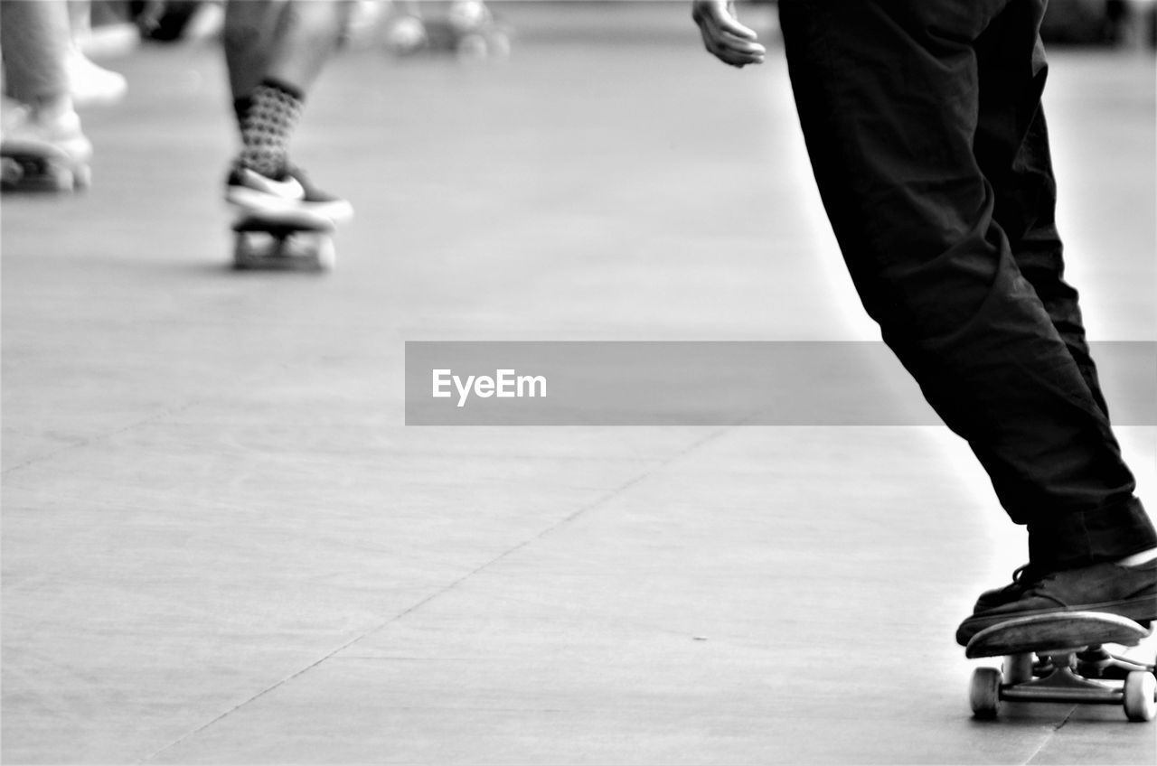 Low section of man skateboarding on floor
