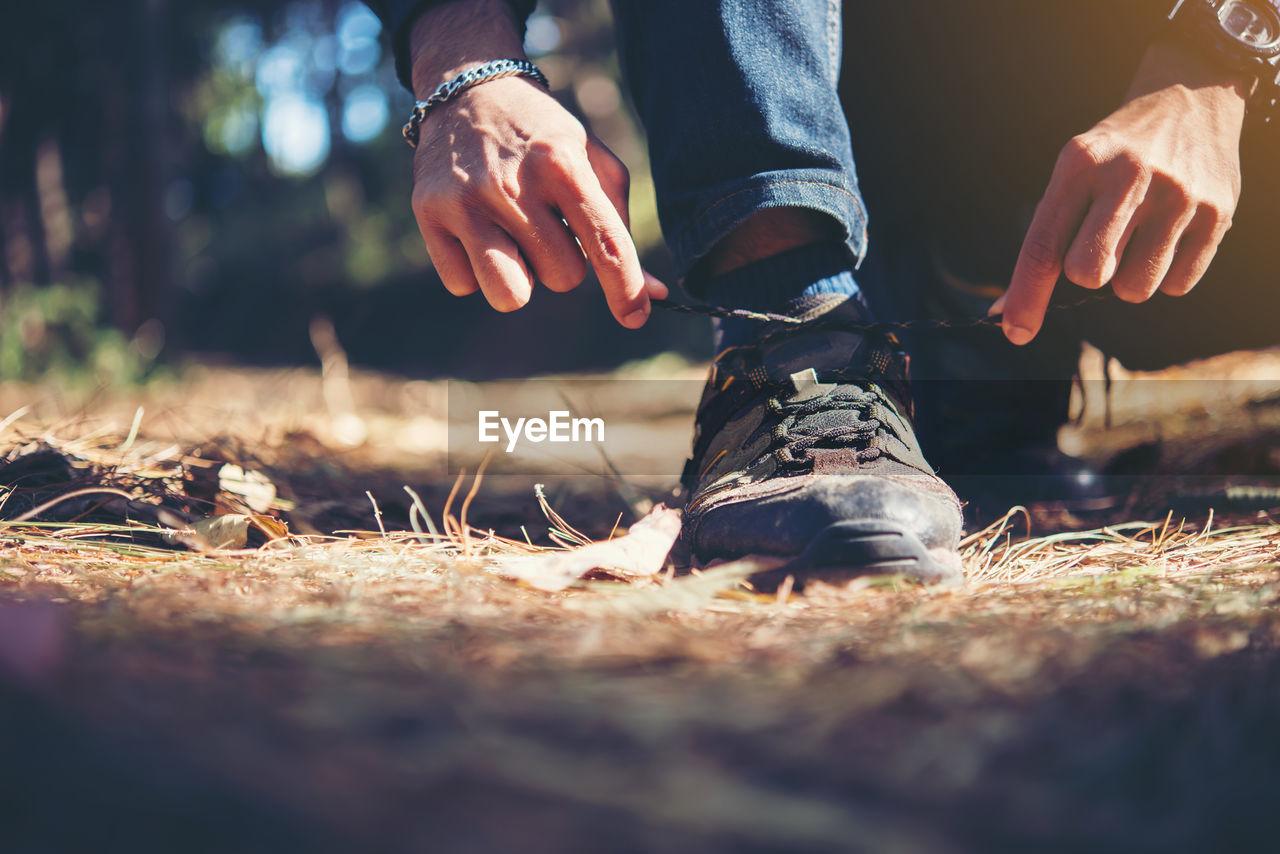 Low section of man tying shoe on field