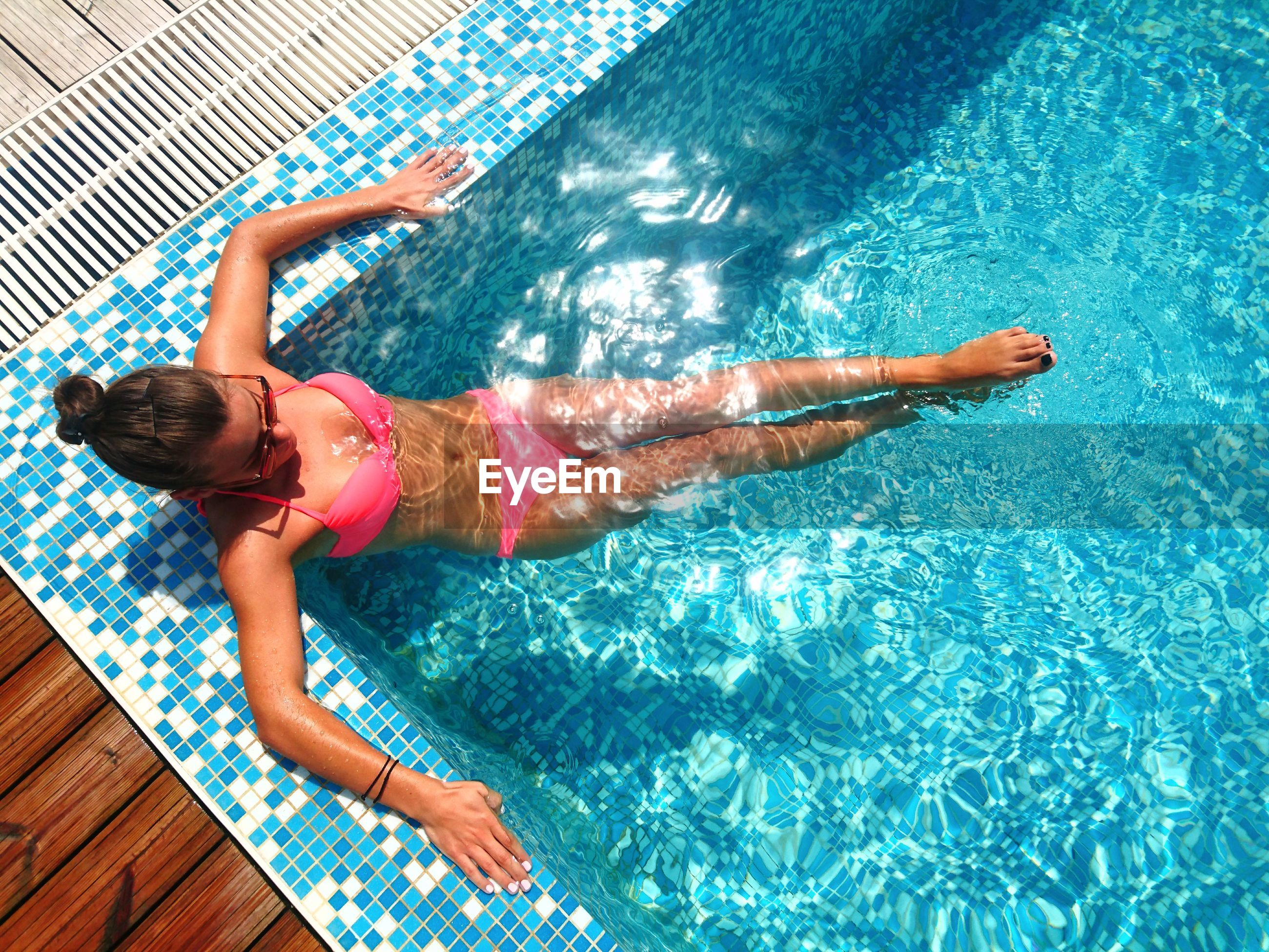 High angle view of young woman wearing pink bikini in swimming pool
