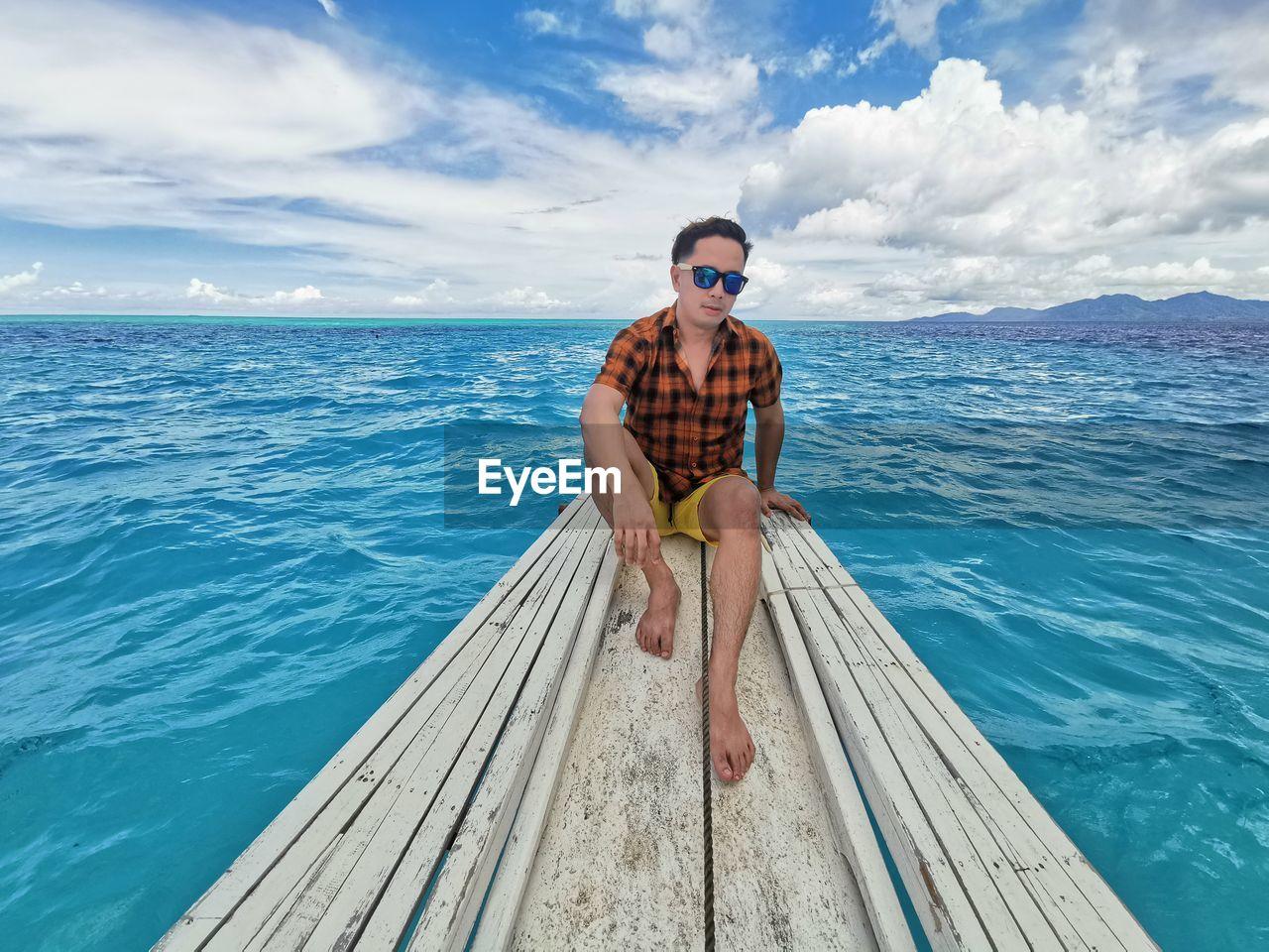 Full length of man sitting on pier over sea against sky