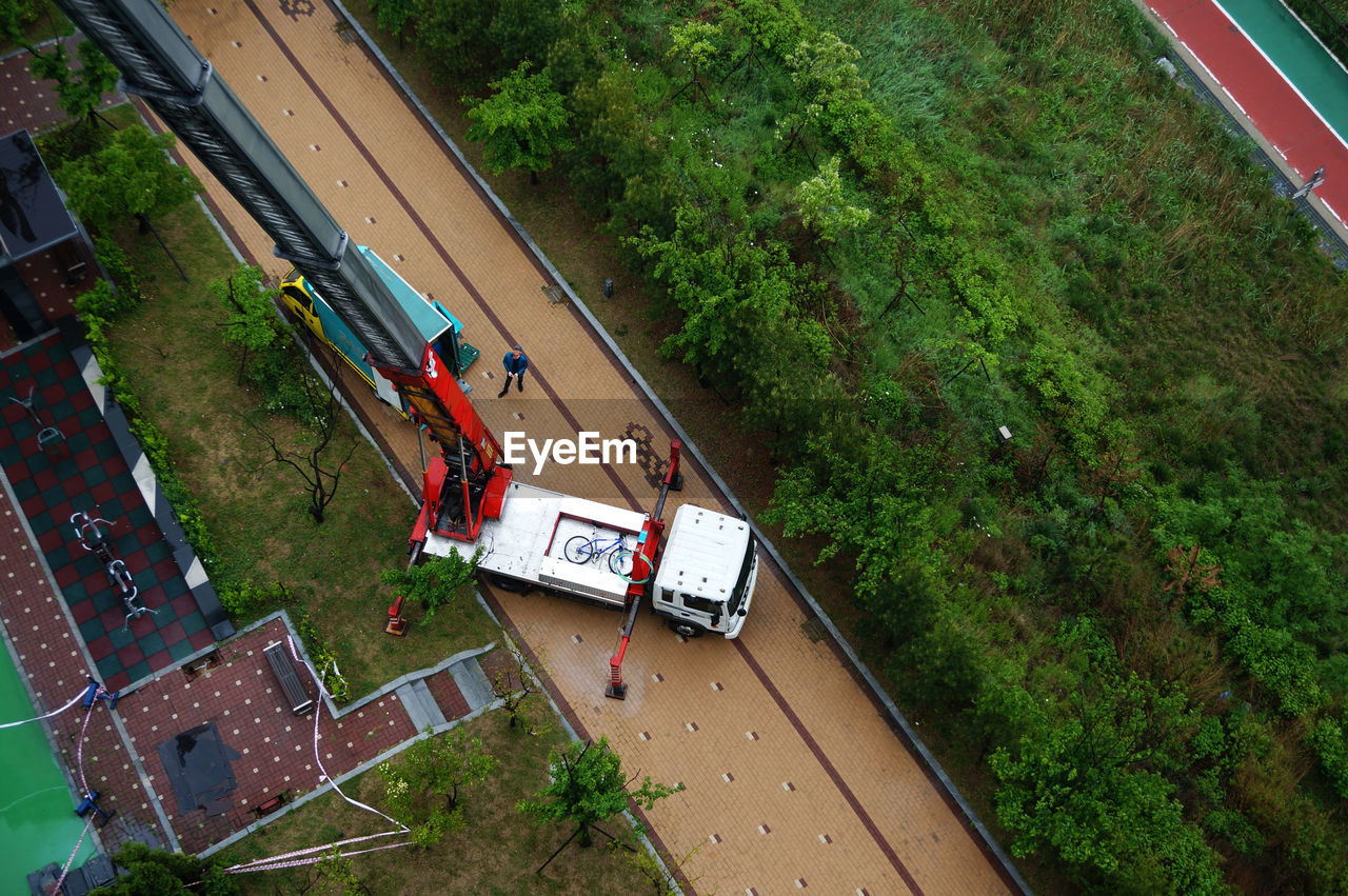 High Angle View Of Cherry Picker Truck On Road By Tree