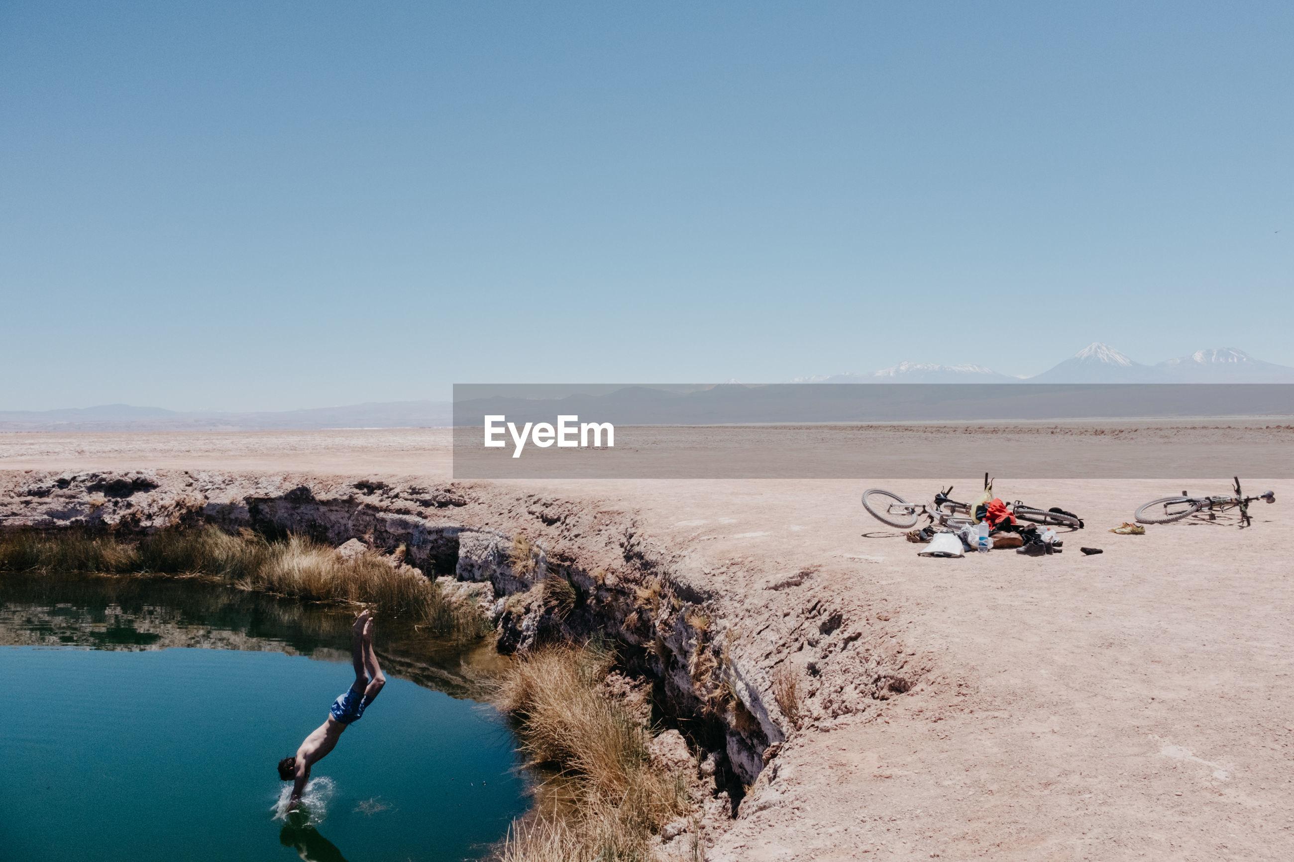 Shirtless man jumping in lake at desert