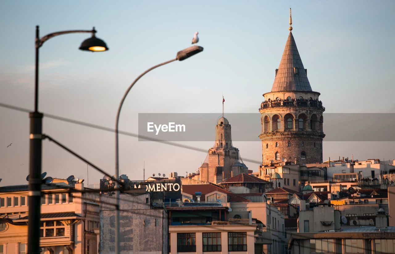 Galata tower amidst buildings against sky at sunset