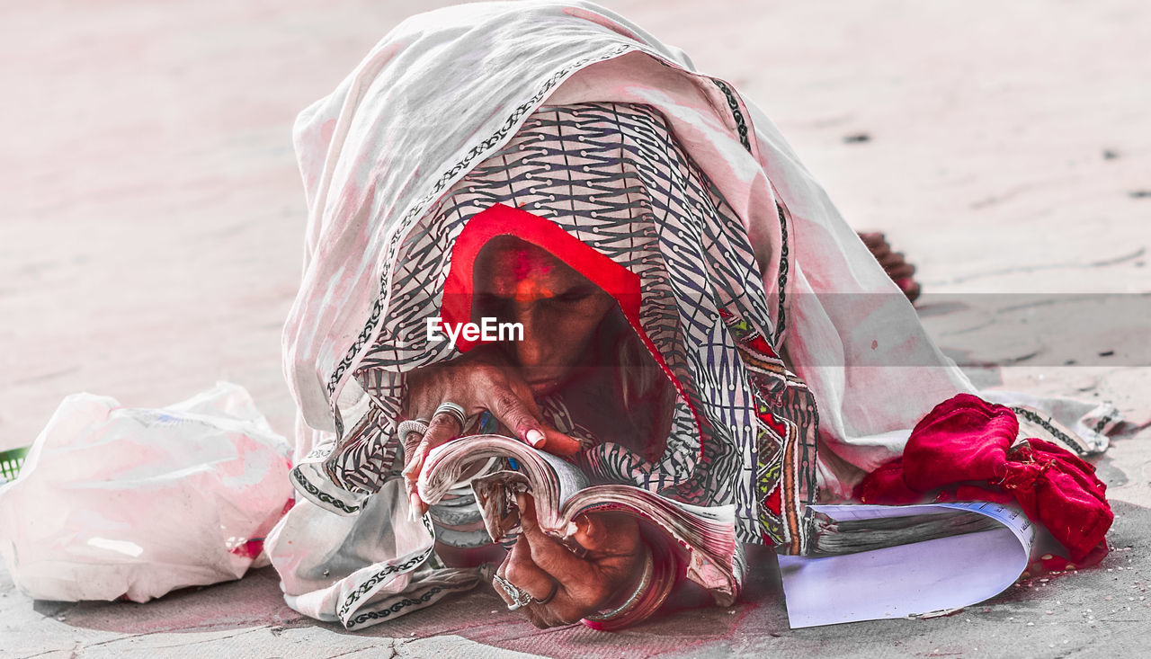 Man Wrapped In Textile While Reading Book On Road