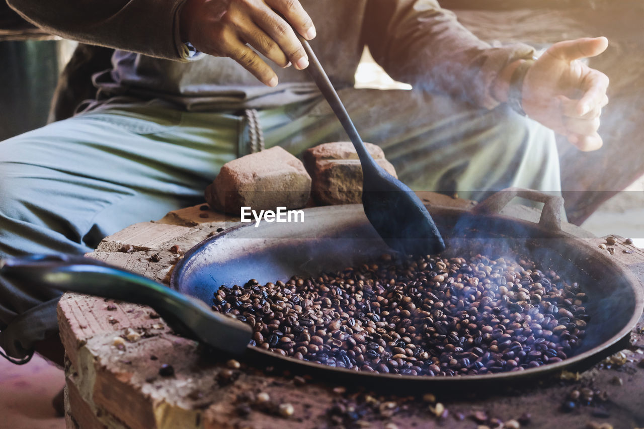 Asian men are sitting roasting coffee beans in a pan on an antique stove
