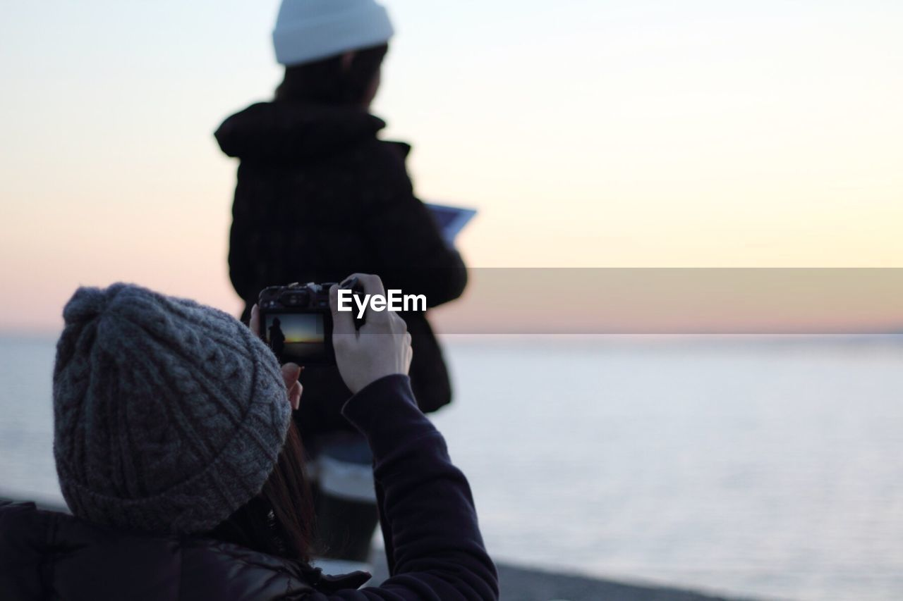 Woman photographing sea against sky during sunset