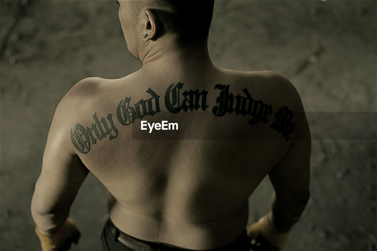 Rear view of shirtless man with tattoo text
