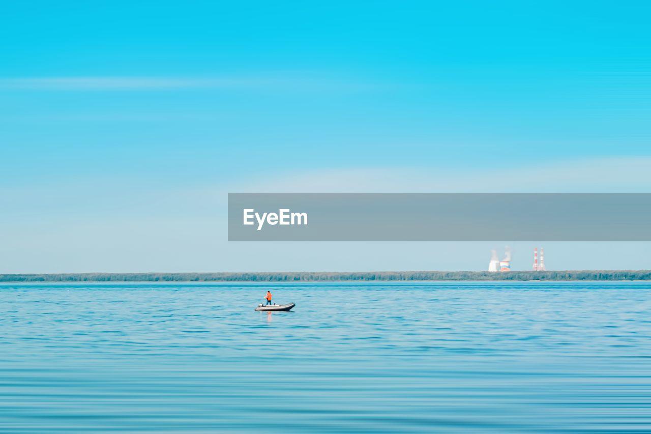 Man in boat in sea against blue sky