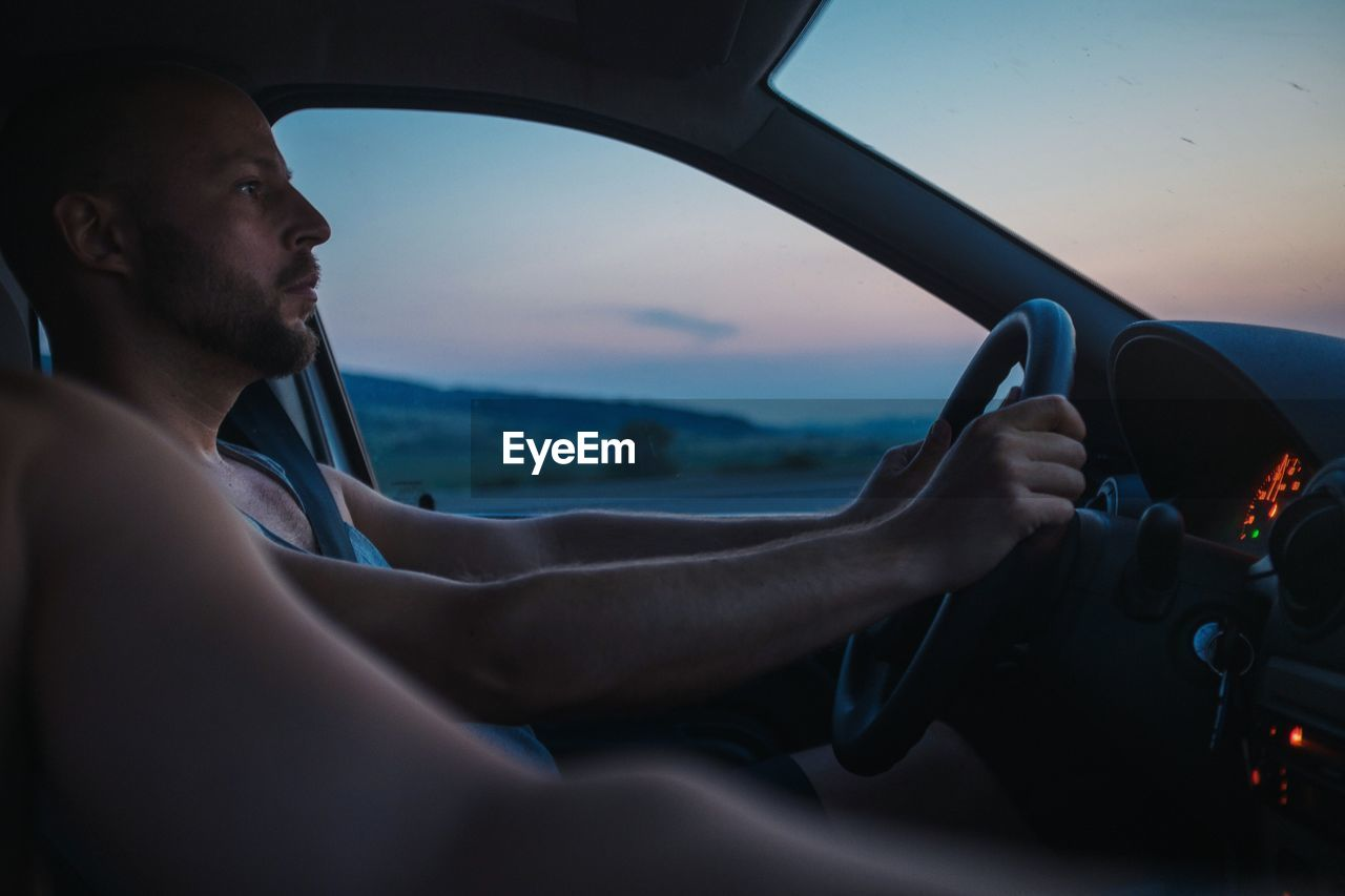 Man With Friend Driving Car During Sunset