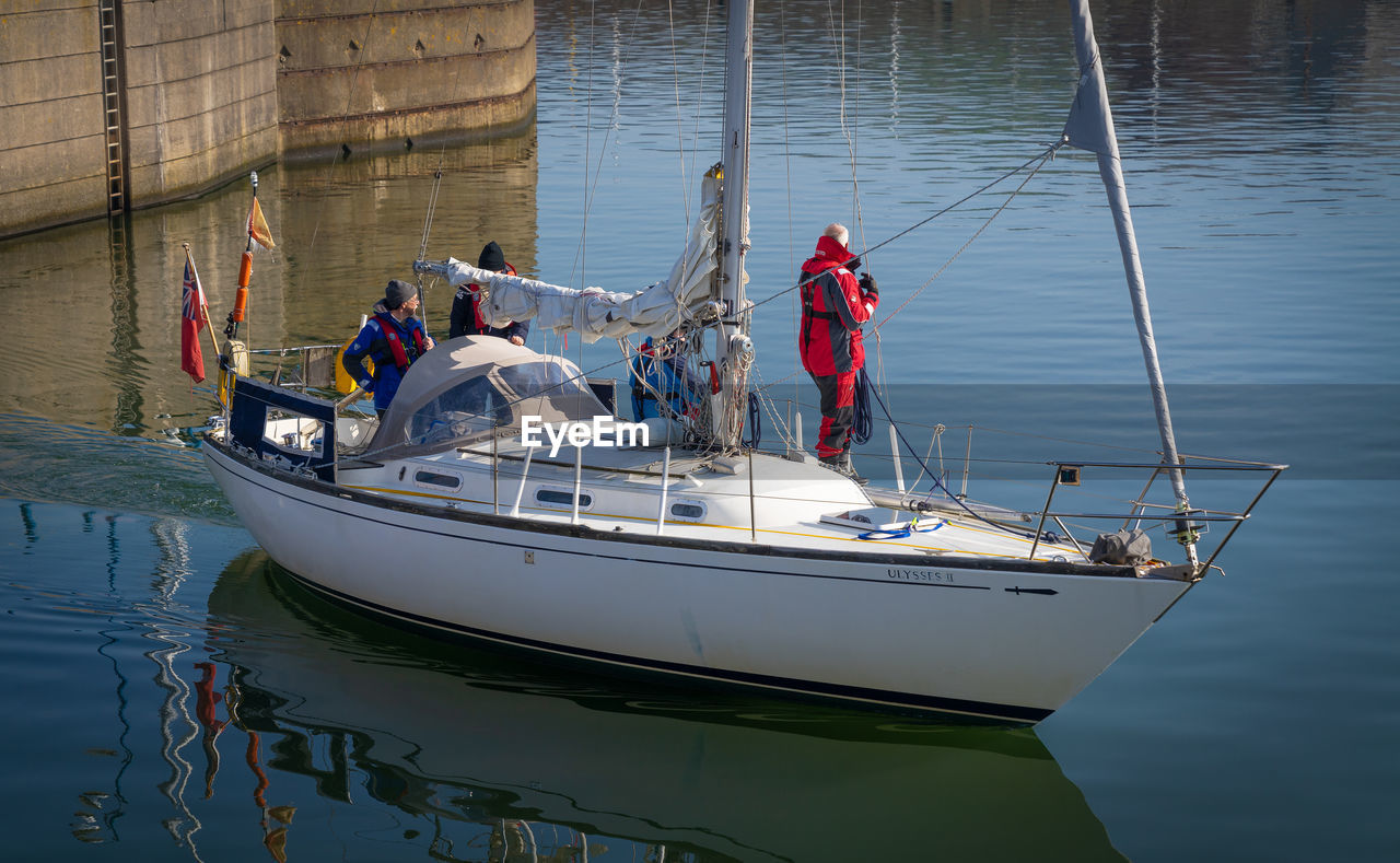 nautical vessel, transportation, mode of transportation, water, waterfront, day, group of people, nature, sea, travel, men, real people, outdoors, moored, standing, occupation, rope, fishing industry, sailboat, luxury