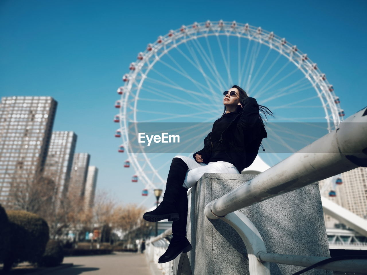 Low angle view of woman sitting on retaining wall against ferris wheel and sky