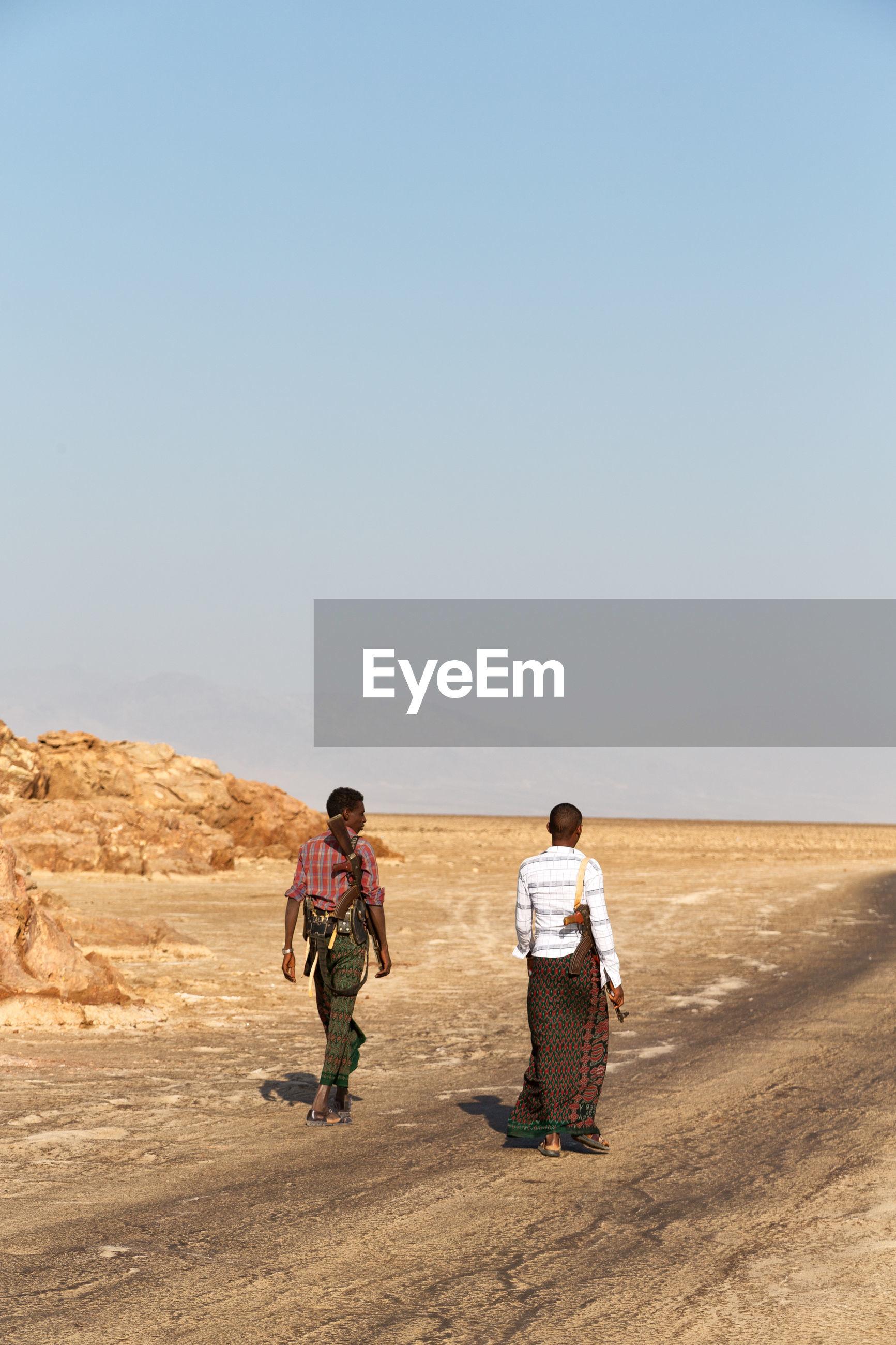 REAR VIEW OF FRIENDS WALKING ON DESERT
