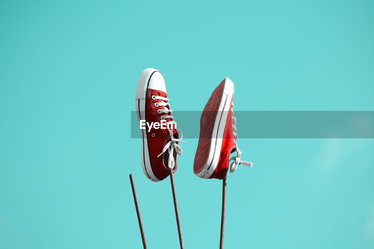 red, copy space, no people, blue, nature, low angle view, day, outdoors, close-up, pattern, arts culture and entertainment, metal, green color, shoe, cut out, sky, flying, sport, single object, still life