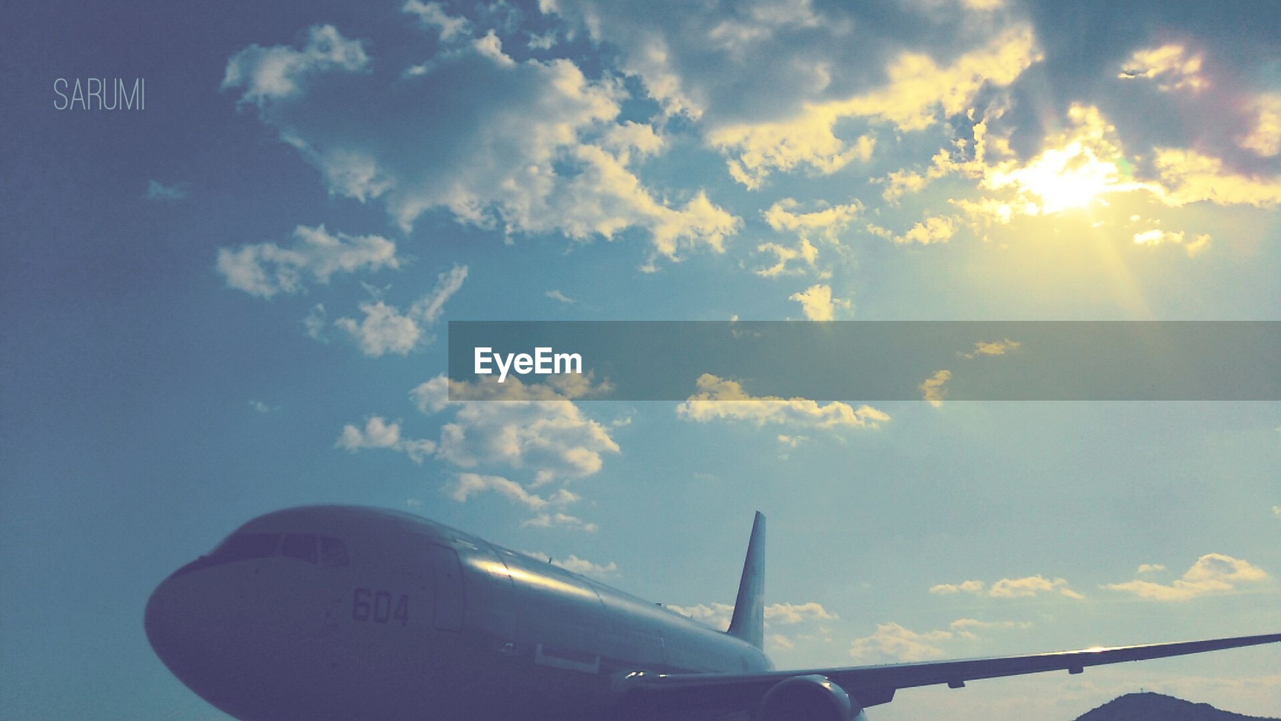 transportation, mode of transport, sky, low angle view, airplane, cloud - sky, air vehicle, part of, cloud, sunlight, cropped, travel, flying, journey, cloudy, aircraft wing, outdoors, sun, day, on the move