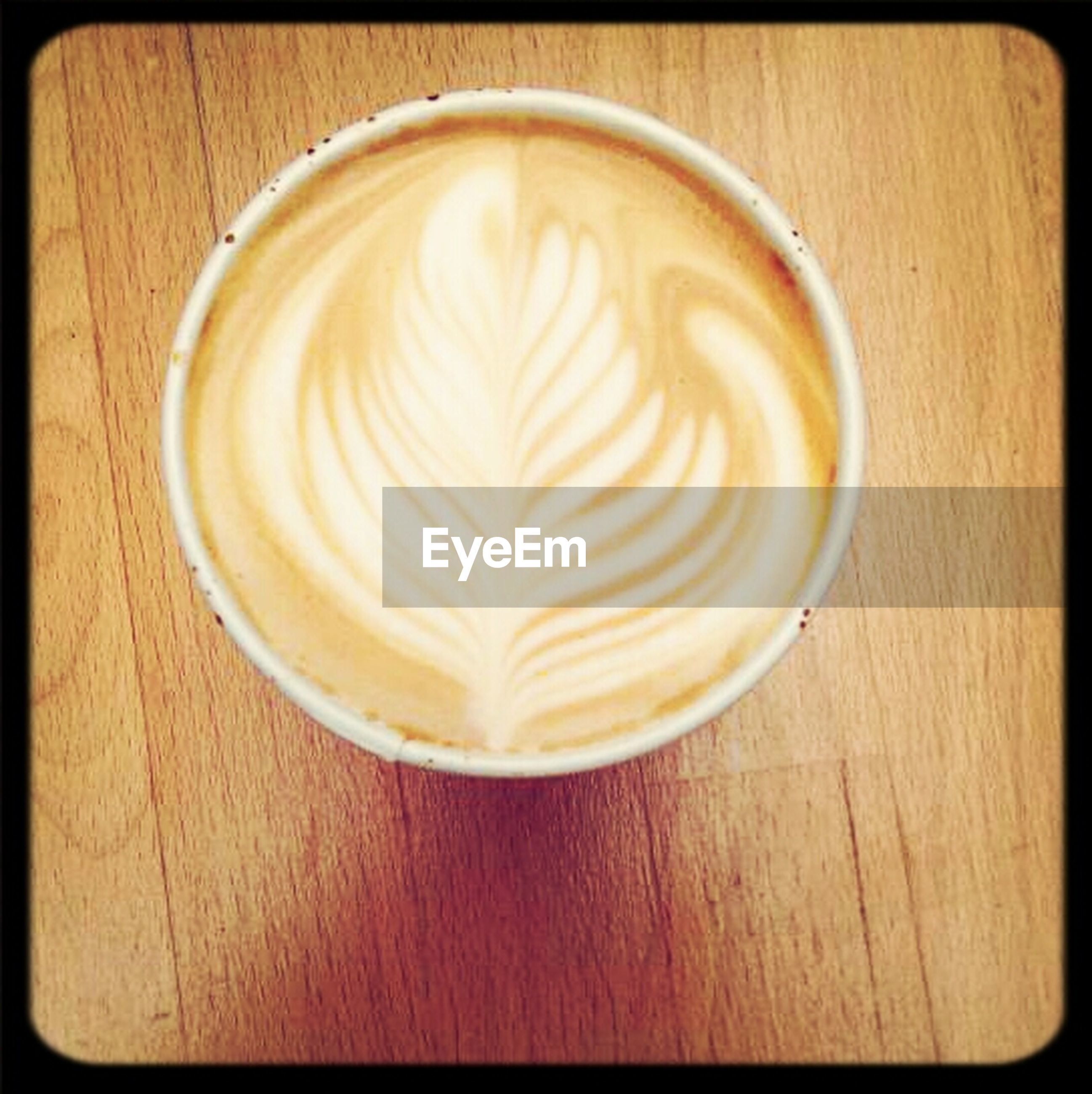 food and drink, table, refreshment, indoors, drink, coffee cup, coffee - drink, transfer print, frothy drink, freshness, froth art, cappuccino, still life, auto post production filter, saucer, wood - material, close-up, high angle view, directly above, heart shape