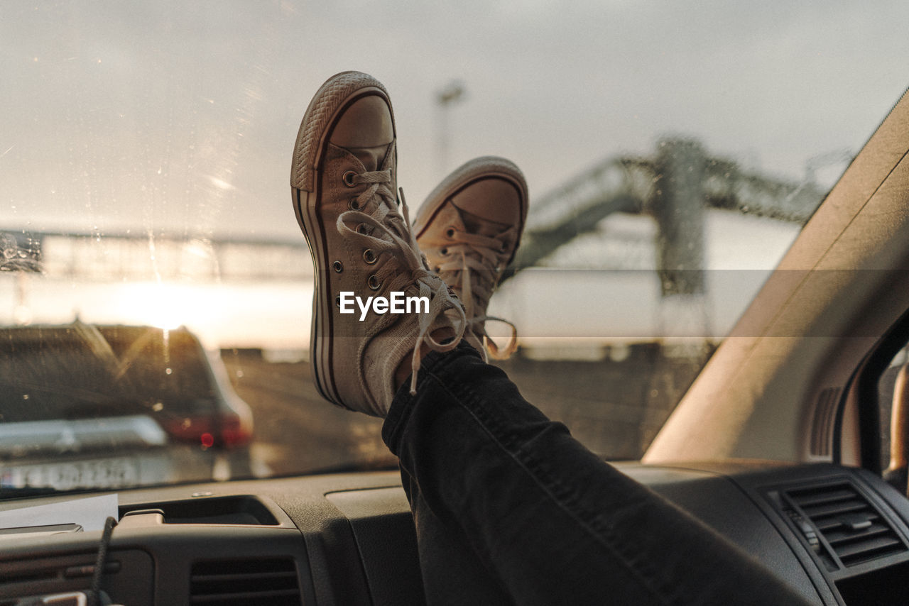 Low section of person wearing shoes on car windshield