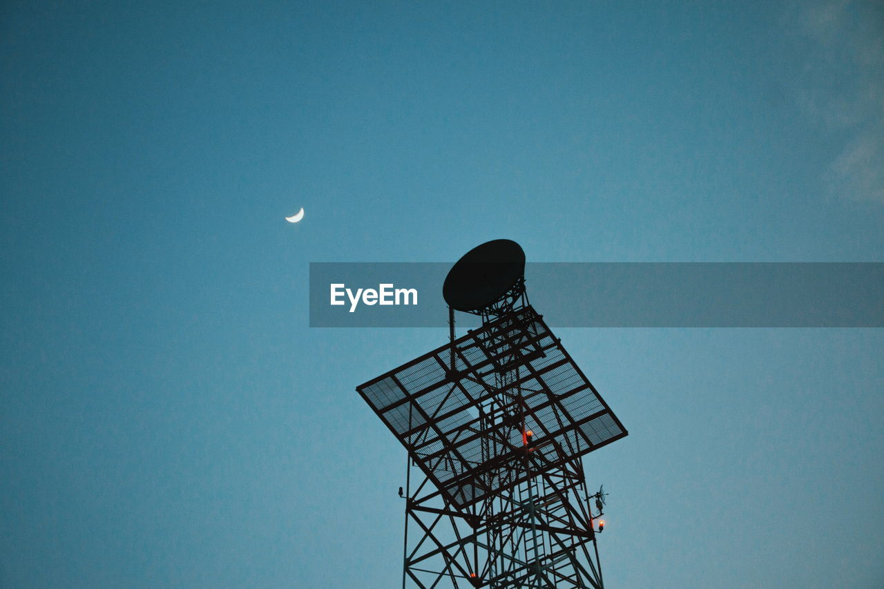 LOW ANGLE VIEW OF COMMUNICATIONS TOWER AGAINST SKY AT DUSK