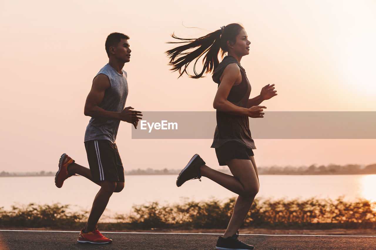 sunset, sky, lifestyles, two people, full length, real people, water, running, young adult, women, side view, young women, motion, leisure activity, sport, adult, people, exercising, togetherness, physical activity