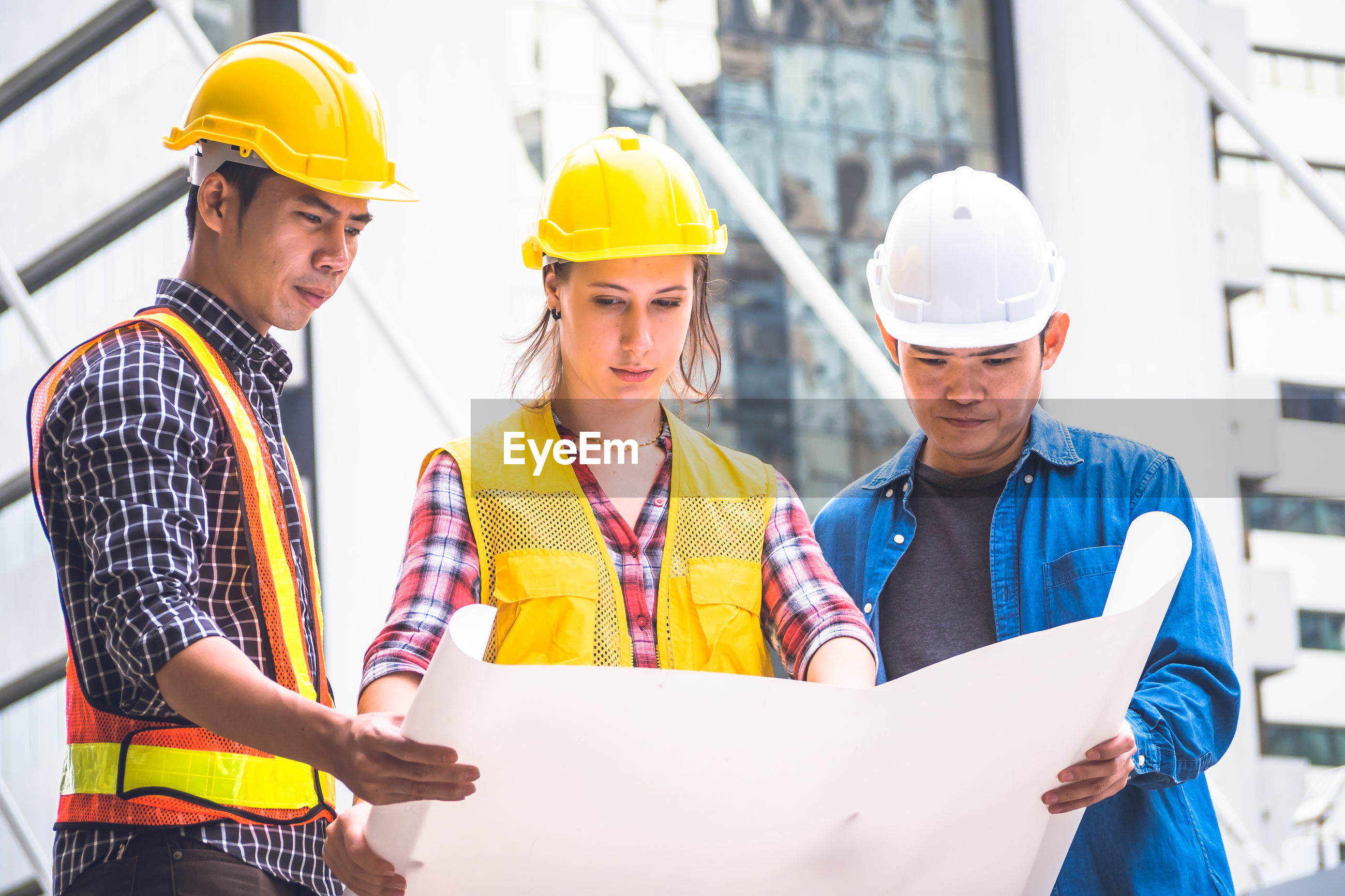 Three engineers looking at blueprint while standing outdoors