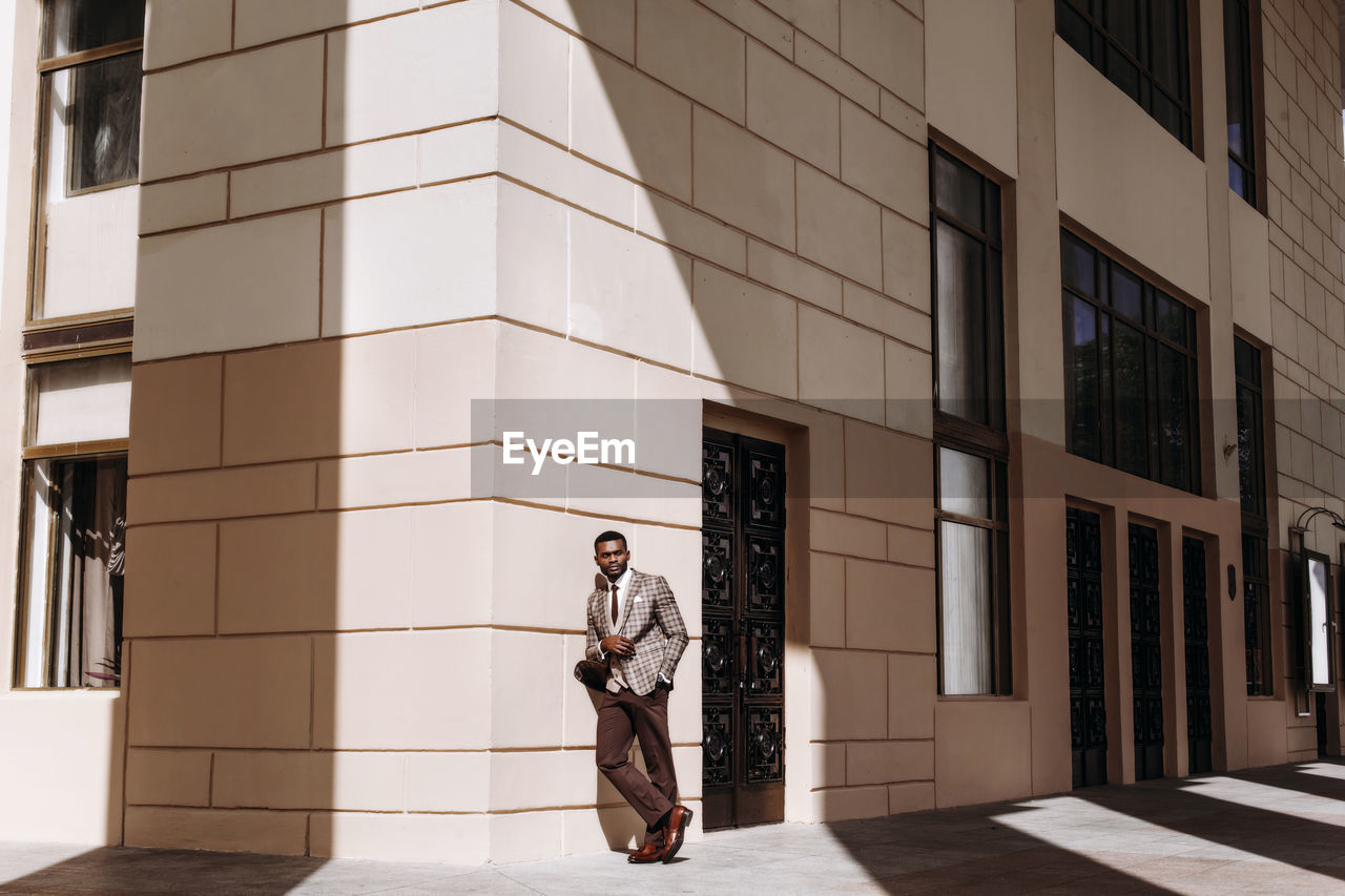 Full length of businessman standing outside building in city