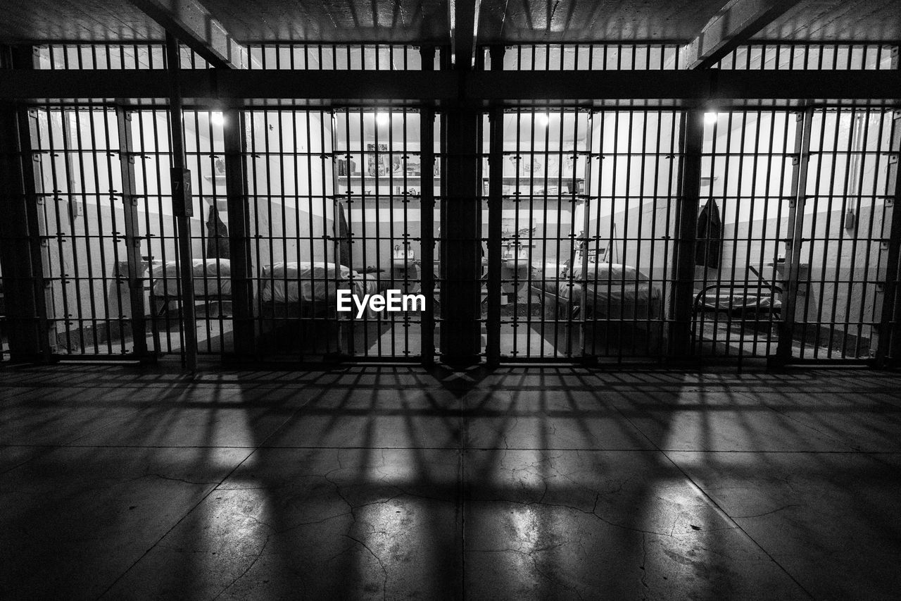 architecture, indoors, window, building, day, flooring, shadow, no people, prison, built structure, sunlight, punishment, domestic room, absence, prison bars, prison cell, warehouse, empty, abandoned, alloy