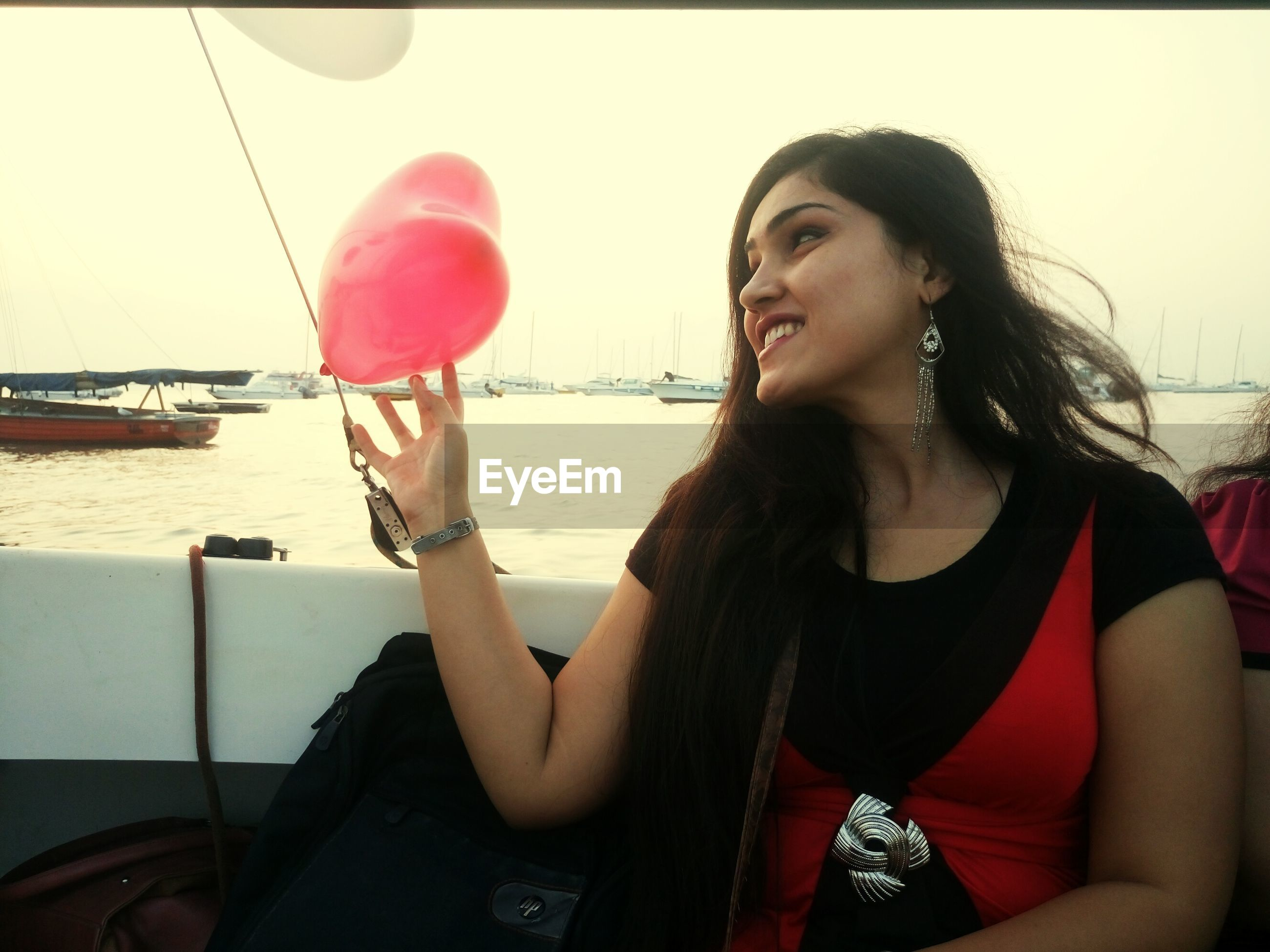 Smiling young woman looking at heart shape balloon in sailboat on sea