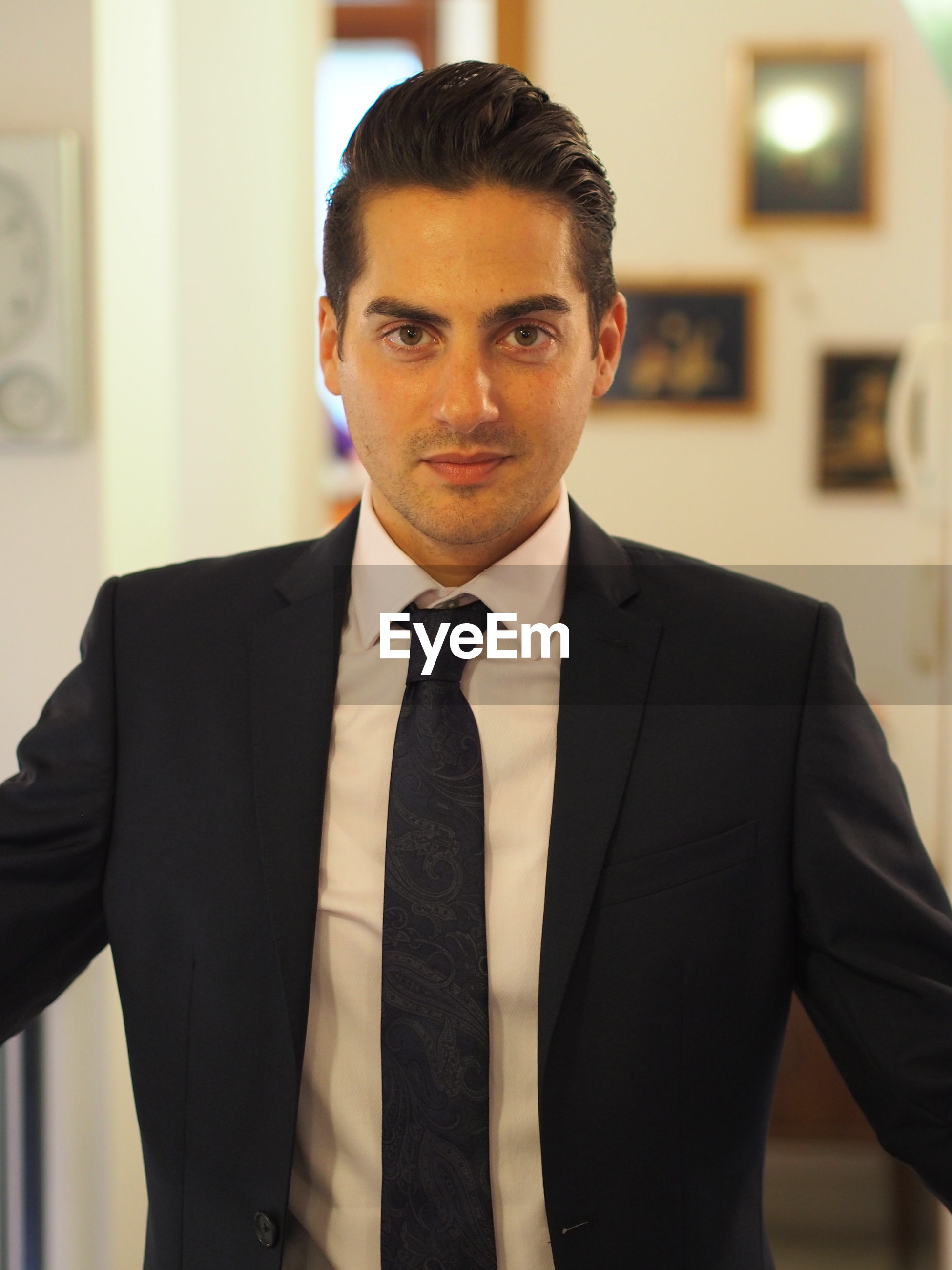 Portrait of mid adult businessman wearing suit while standing at home