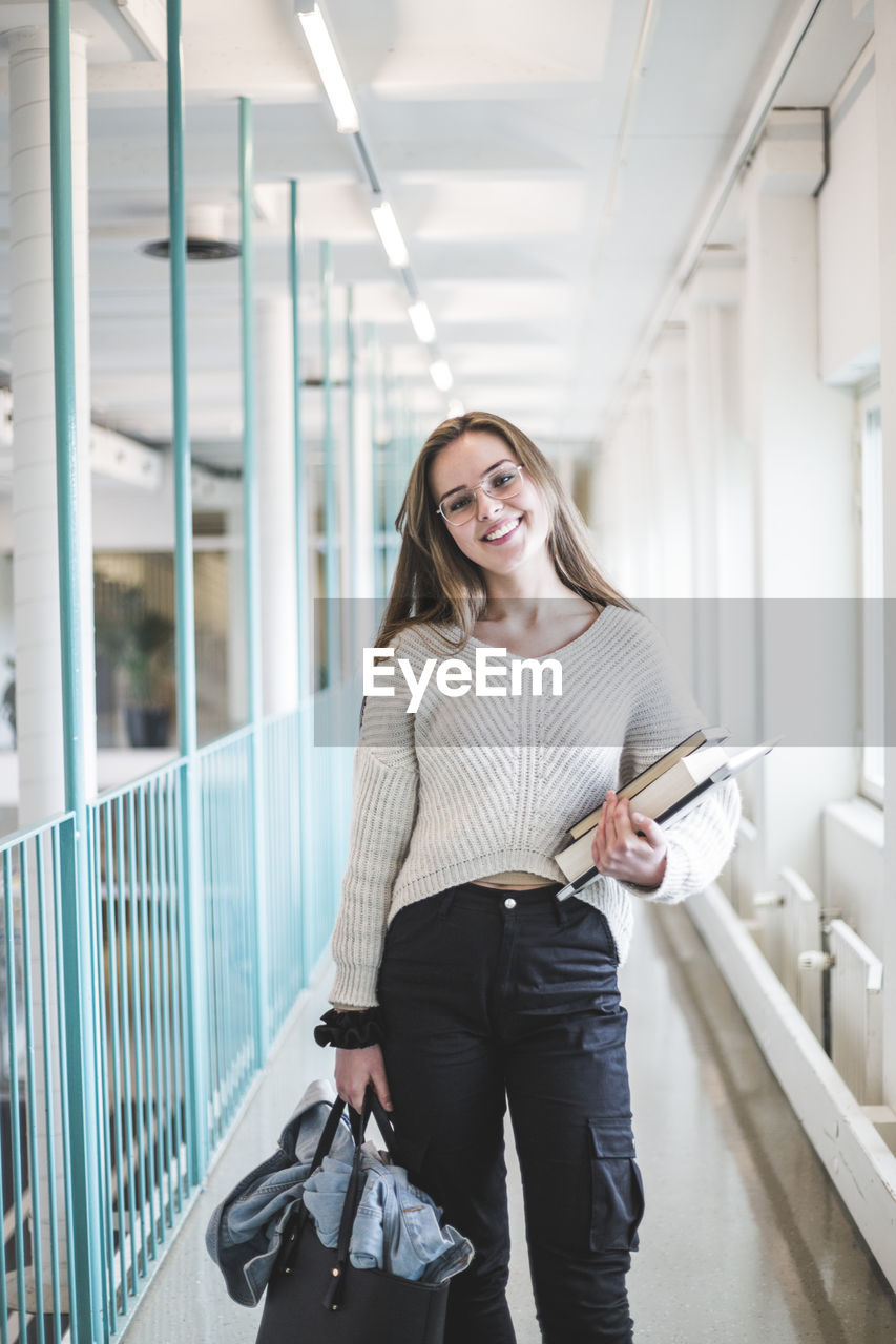 PORTRAIT OF A SMILING YOUNG WOMAN USING PHONE IN CORRIDOR