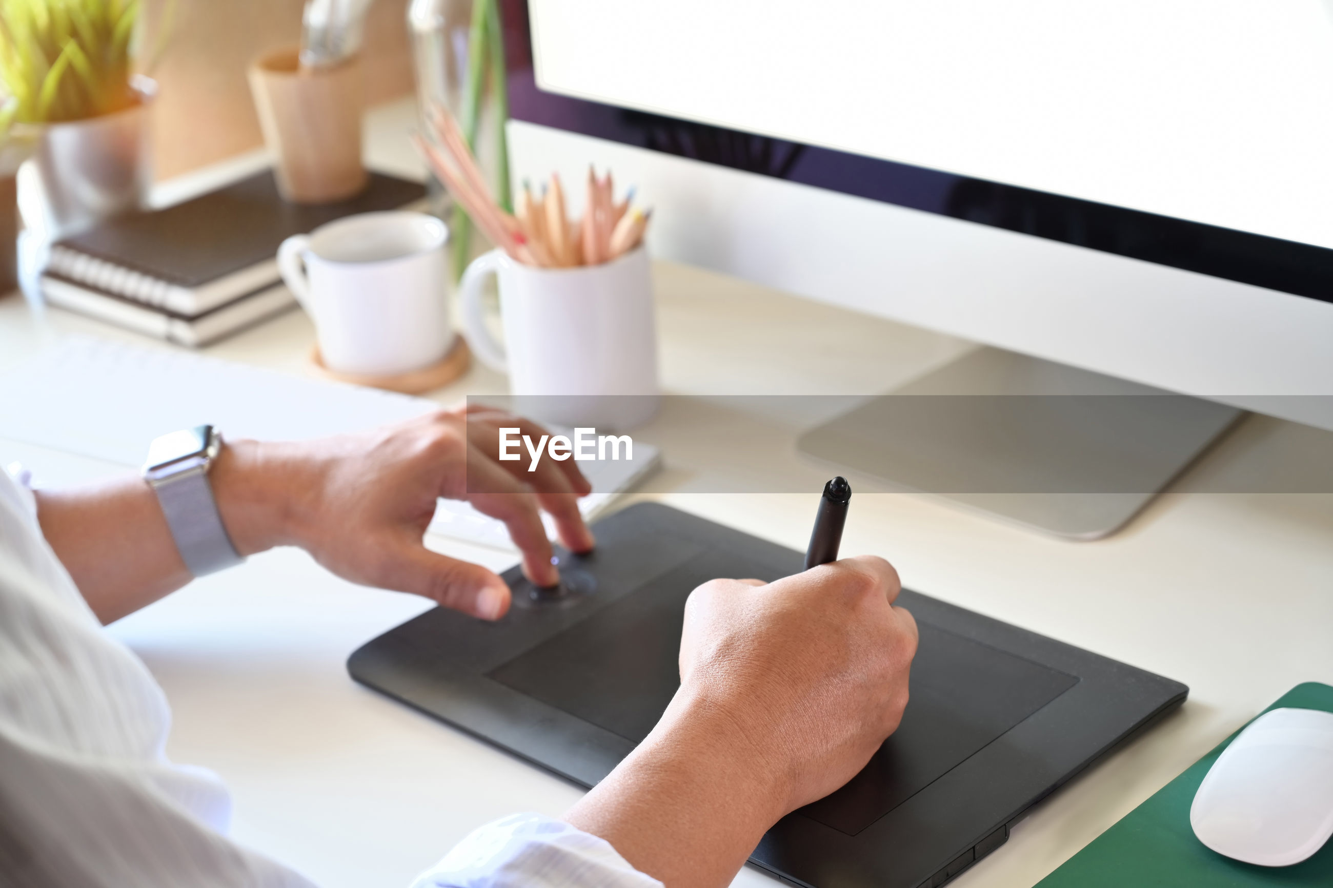 Cropped hands of man using graphics tablet on table