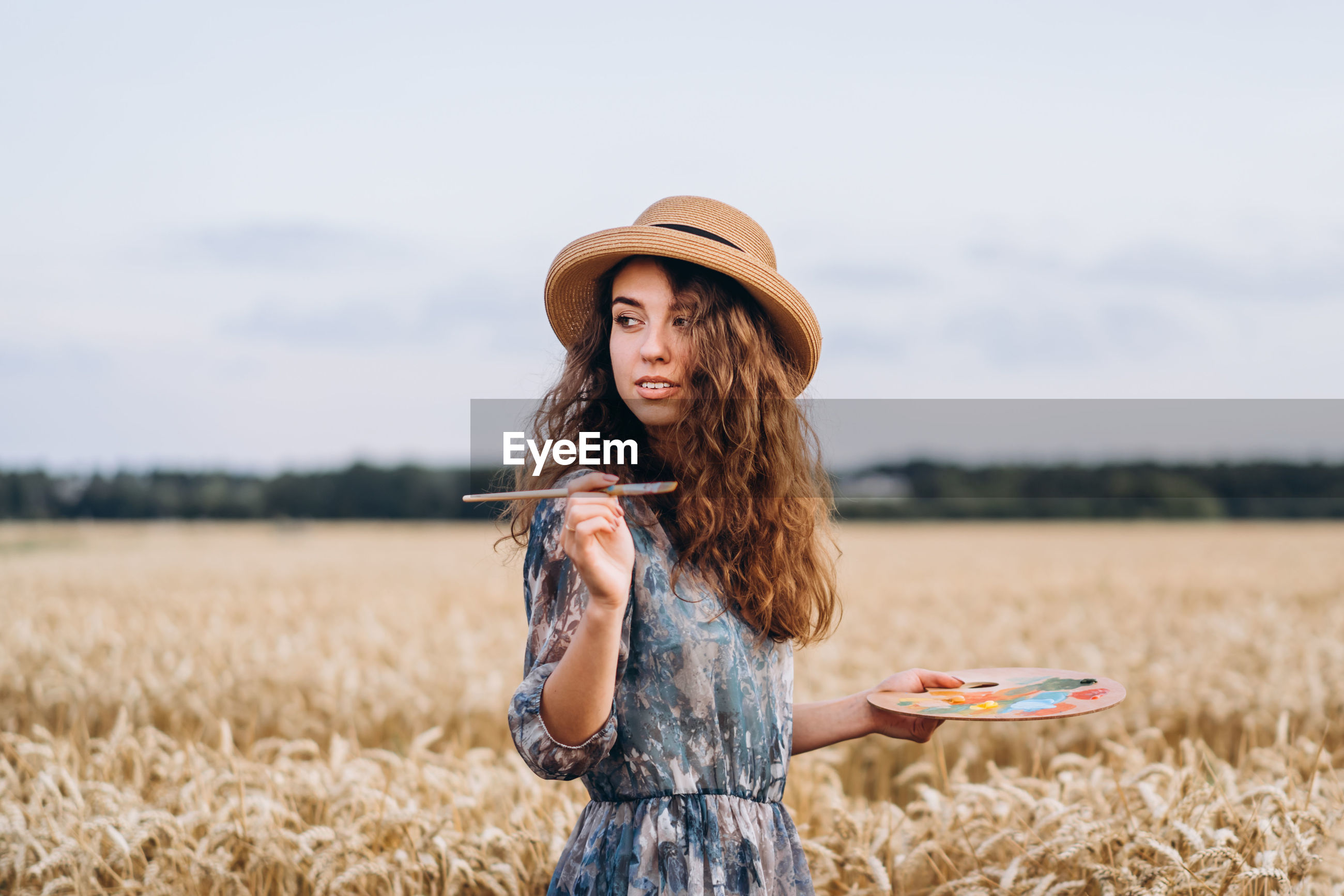Young woman wearing hat while standing on field