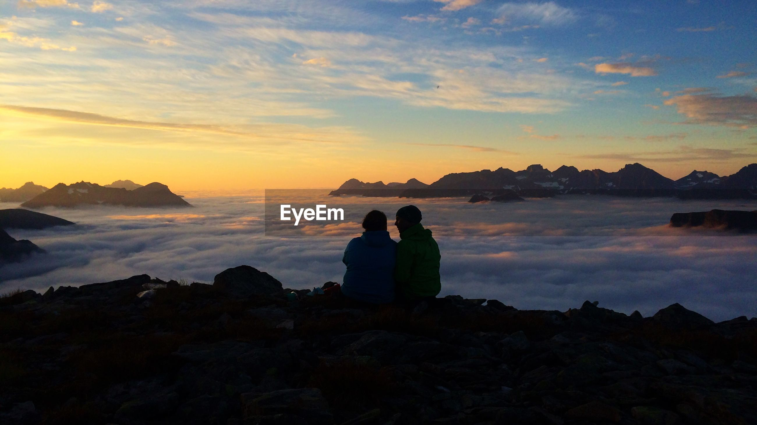 Rear view of people on mountain in foggy weather at hjorundfjord against sky