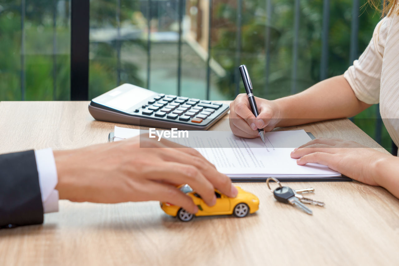 Midsection of man holding toy car while woman signing document