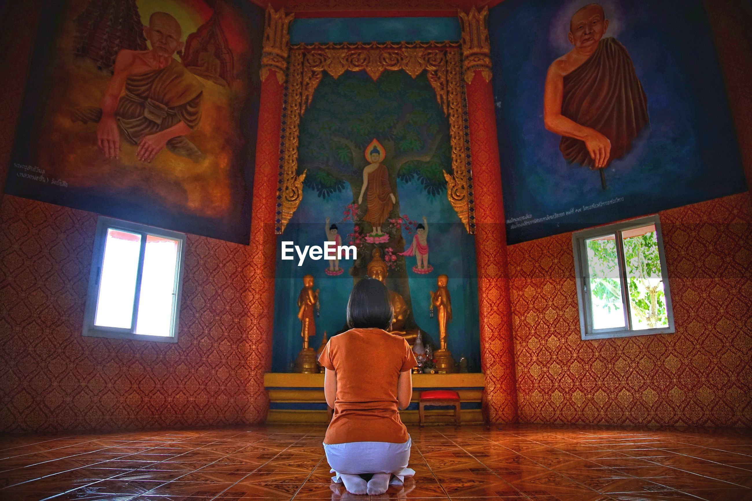 Rear view of woman praying in buddhist temple