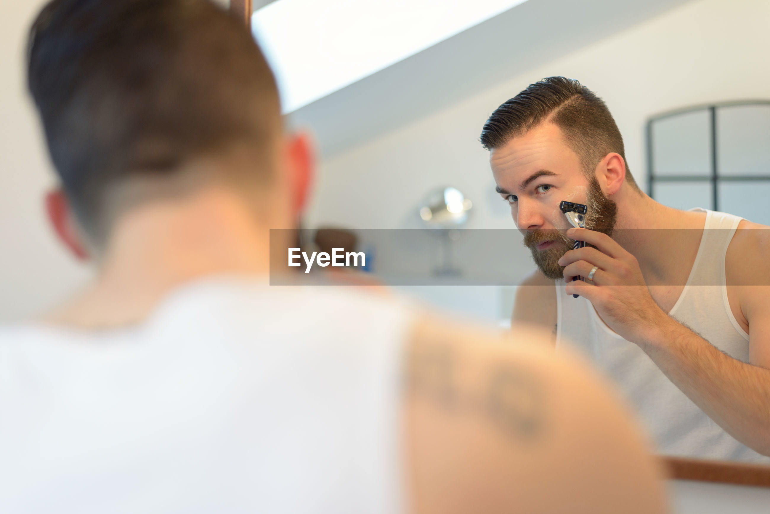 Young man shaving beard at home