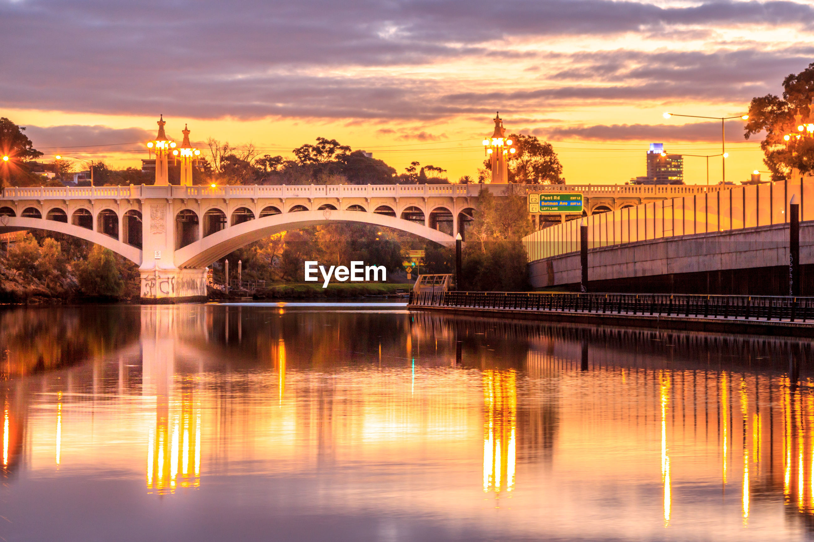 Illuminated arch bridge over river against cloudy sky during sunset
