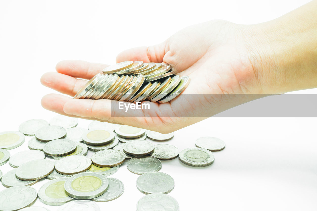 Cropped hands holding coins over white background