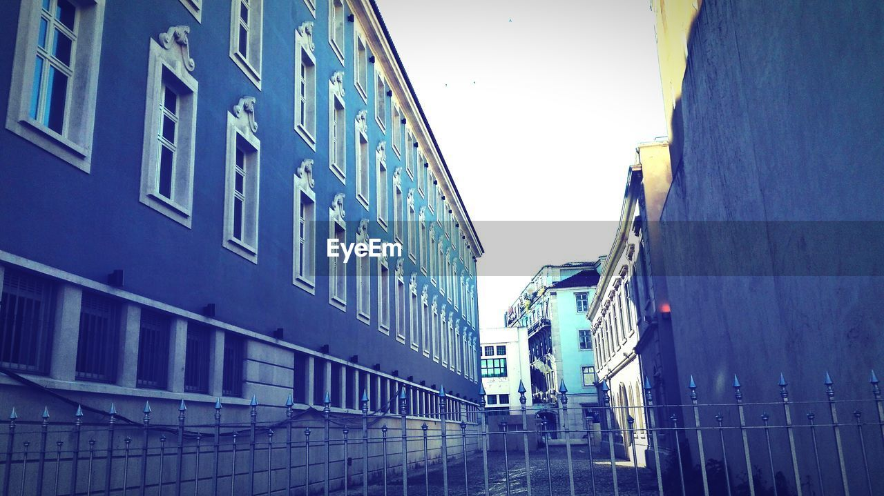 Low Angle View Of Buildings In Front Of Fence