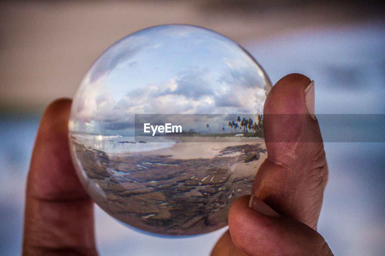 human hand, one person, human finger, human body part, real people, holding, personal perspective, focus on foreground, close-up, crystal ball, leisure activity, outdoors, sky, men, day, fragility, people