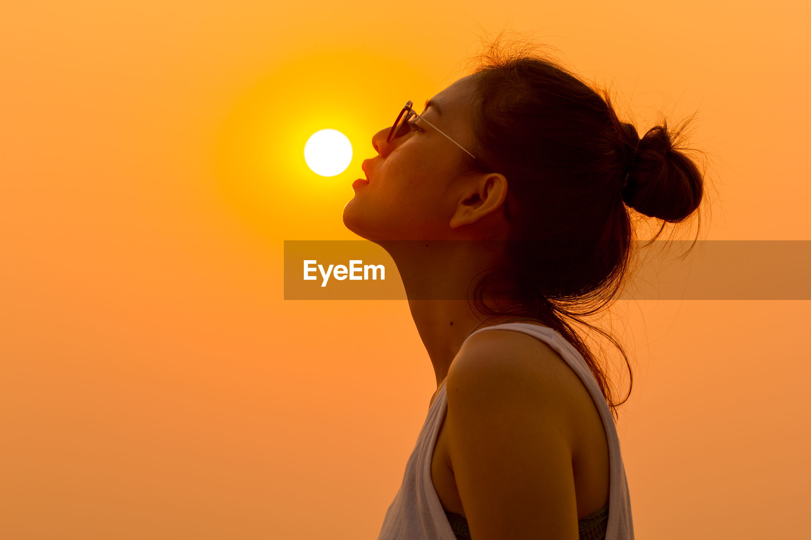 Optical illusion of woman reaching sun against clear sky during sunset
