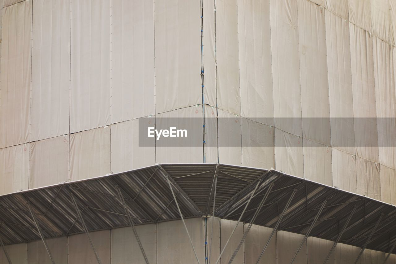 Low angle view of building covered with tarpaulins at construction site