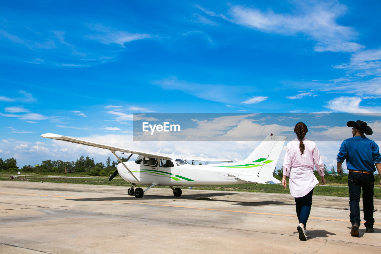 air vehicle, airplane, transportation, airport, sky, cloud - sky, mode of transportation, travel, men, full length, airport runway, nature, rear view, day, adult, people, blue, women, real people, outdoors, private airplane, corporate jet, aerospace industry