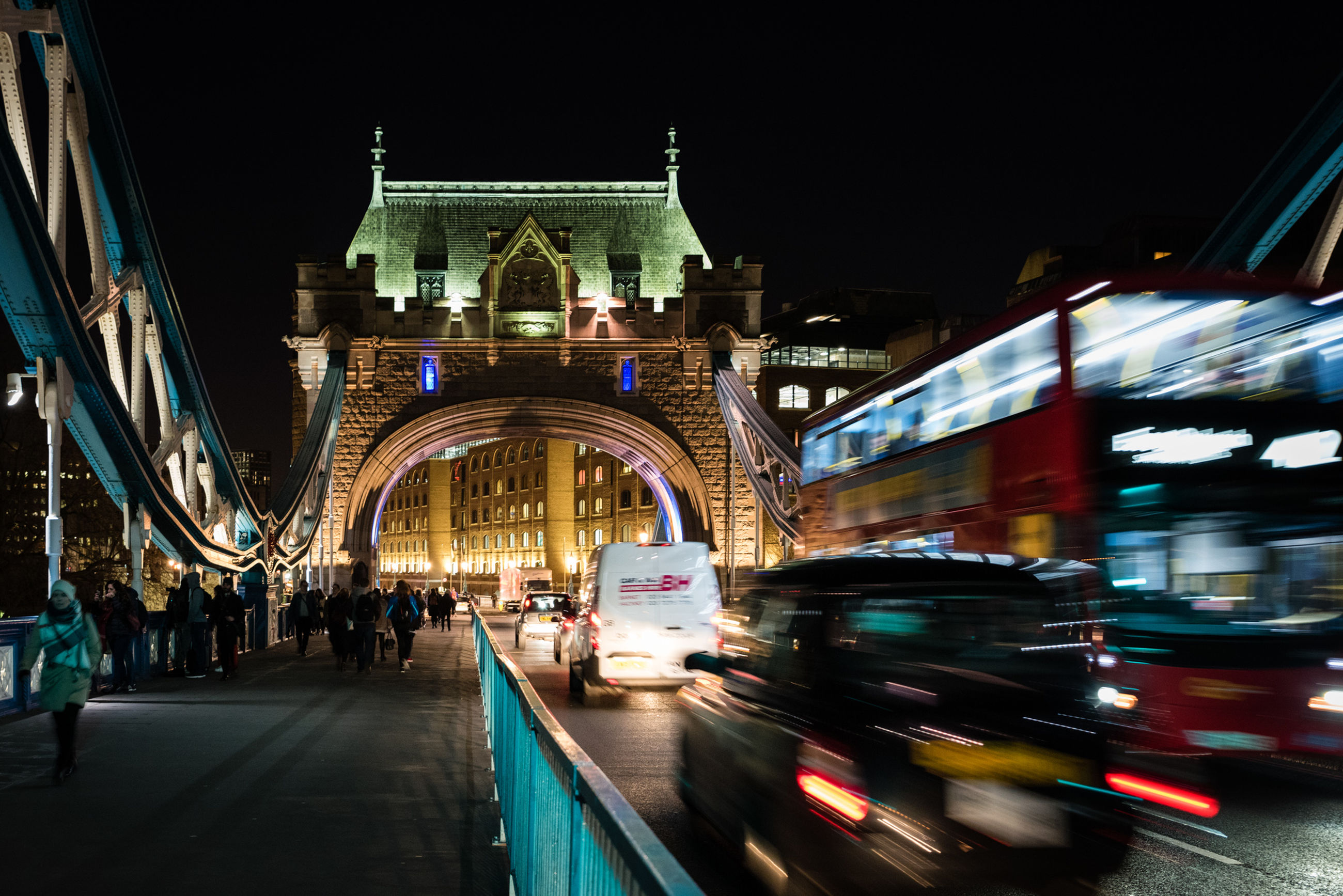 Bus and car on tower bridge in city at night