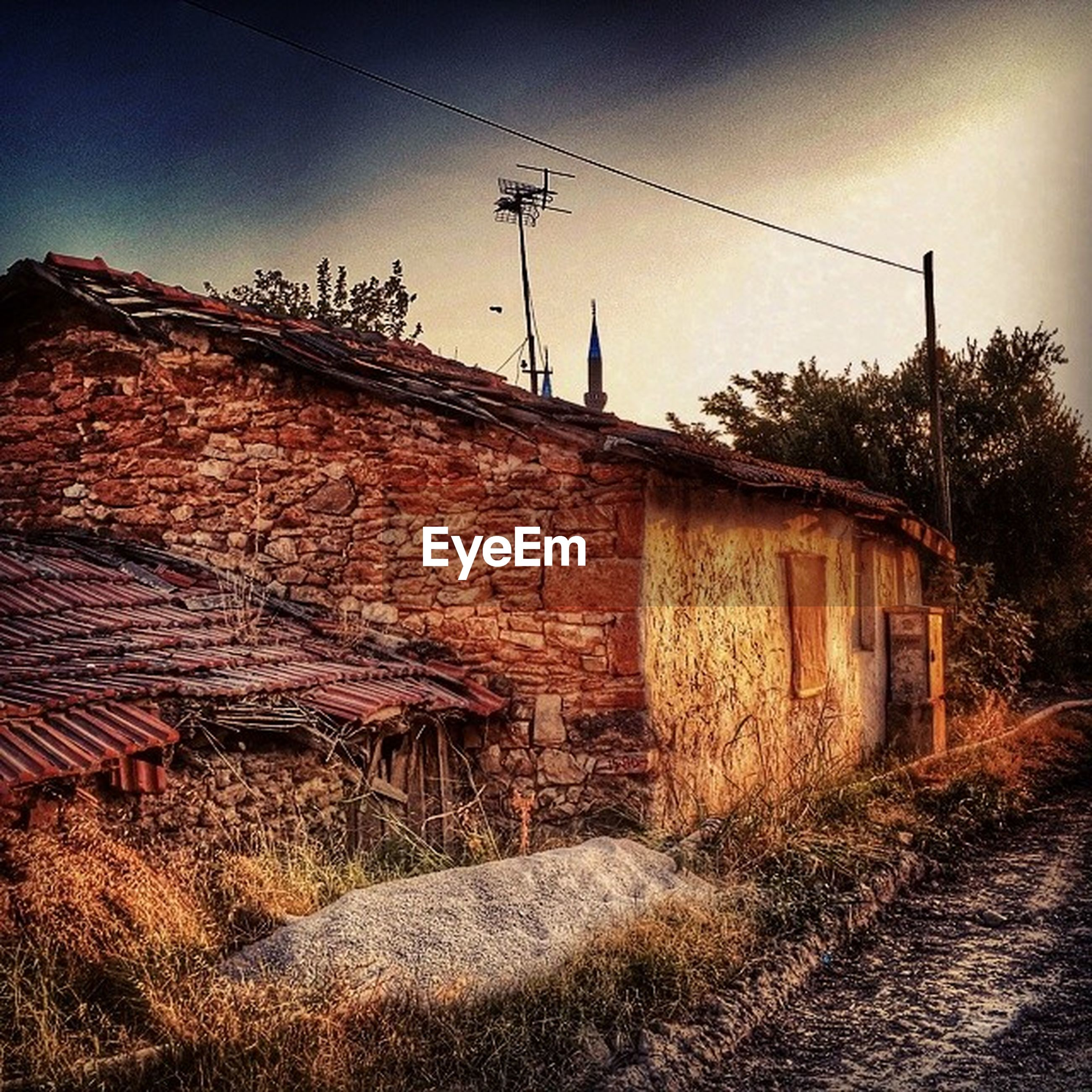 architecture, built structure, building exterior, house, sky, old, abandoned, brick wall, rural scene, obsolete, low angle view, outdoors, day, residential structure, run-down, damaged, no people, deterioration, field, electricity pylon