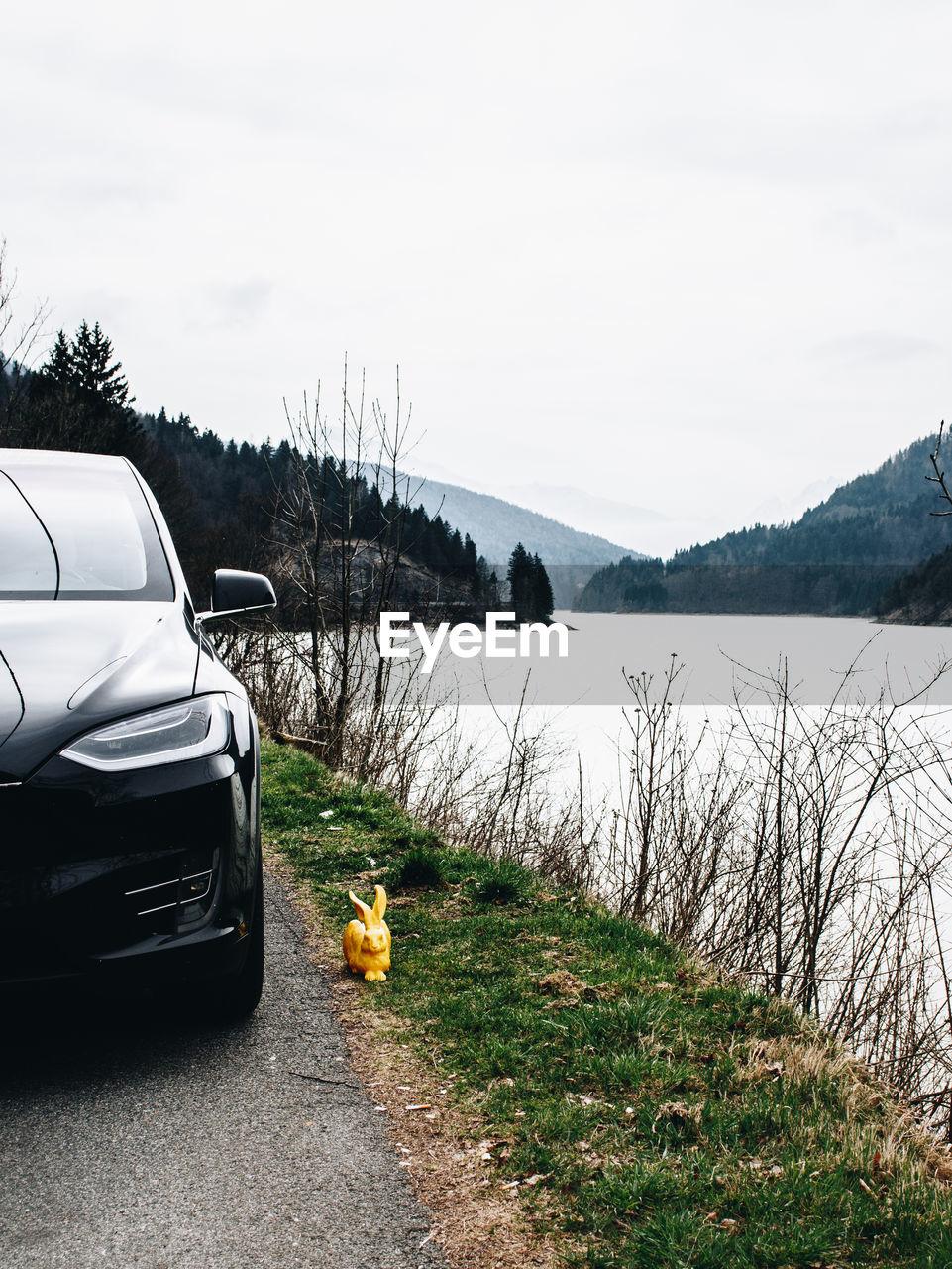 CAR ON LAKE AGAINST SKY