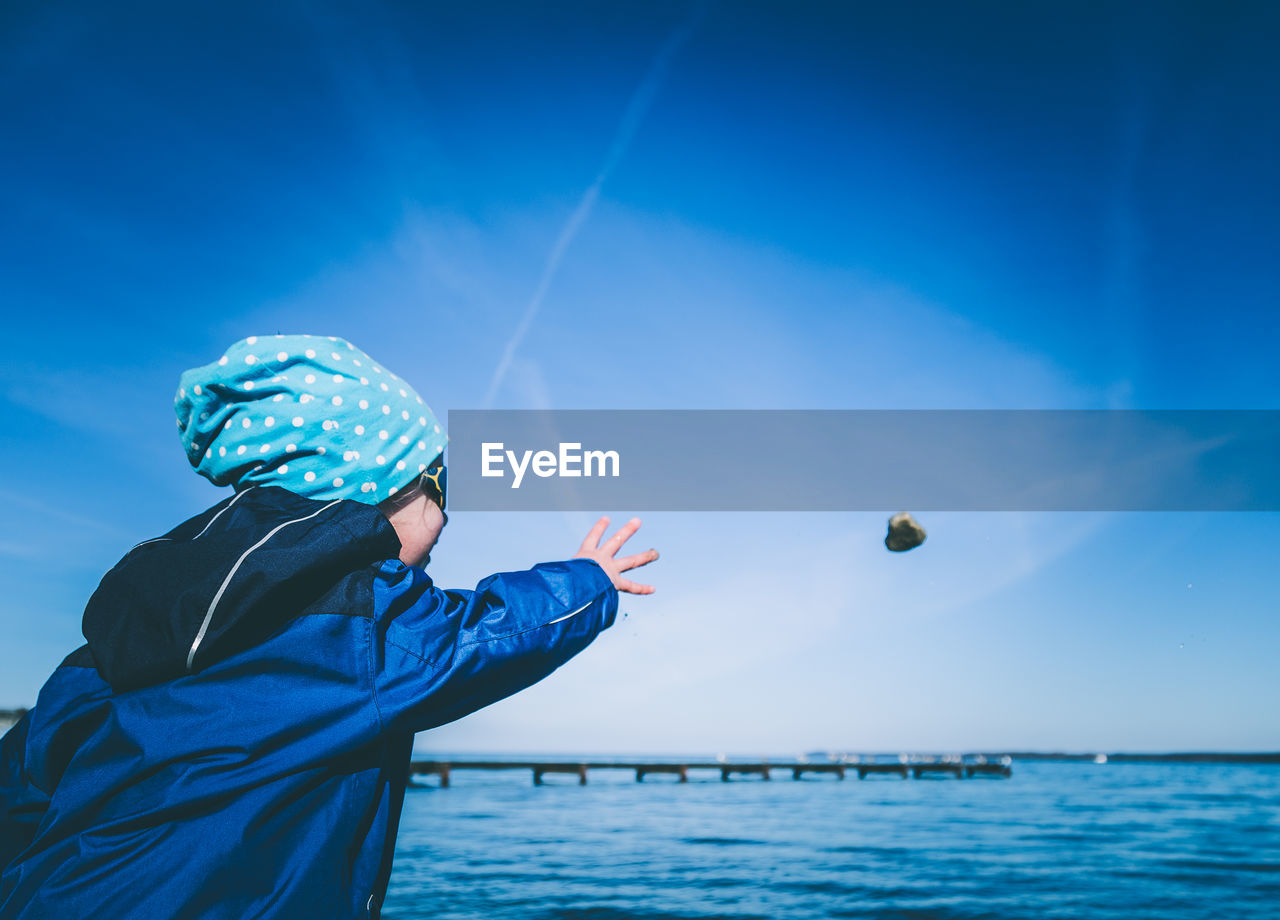 Child Throwing Rock In Sea Against Blue Sky