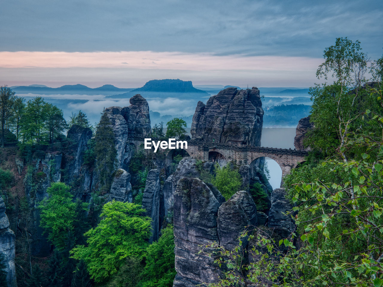 sky, tree, nature, travel, beauty in nature, travel destinations, plant, cloud - sky, architecture, mountain, built structure, rock formation, scenics - nature, tourism, rock, no people, day, water, tranquil scene, solid, outdoors, arch bridge, formation