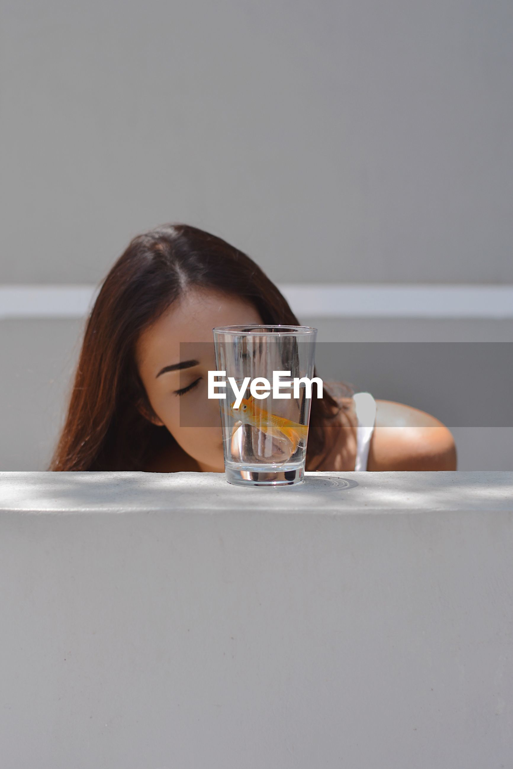 PORTRAIT OF YOUNG WOMAN DRINKING GLASSES