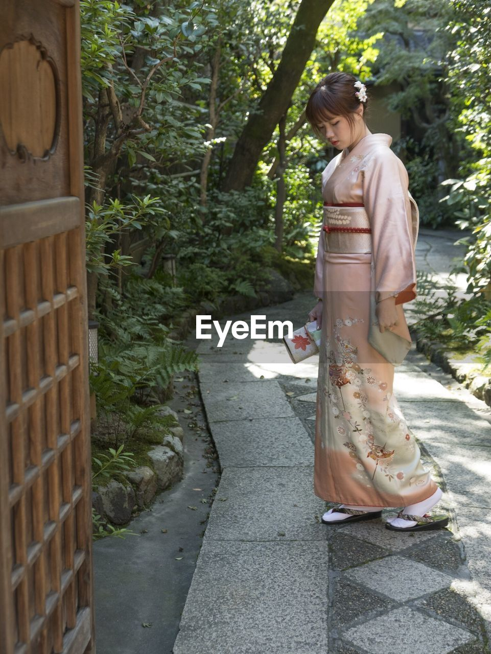 Young woman standing in kimono on footpath amidst plants