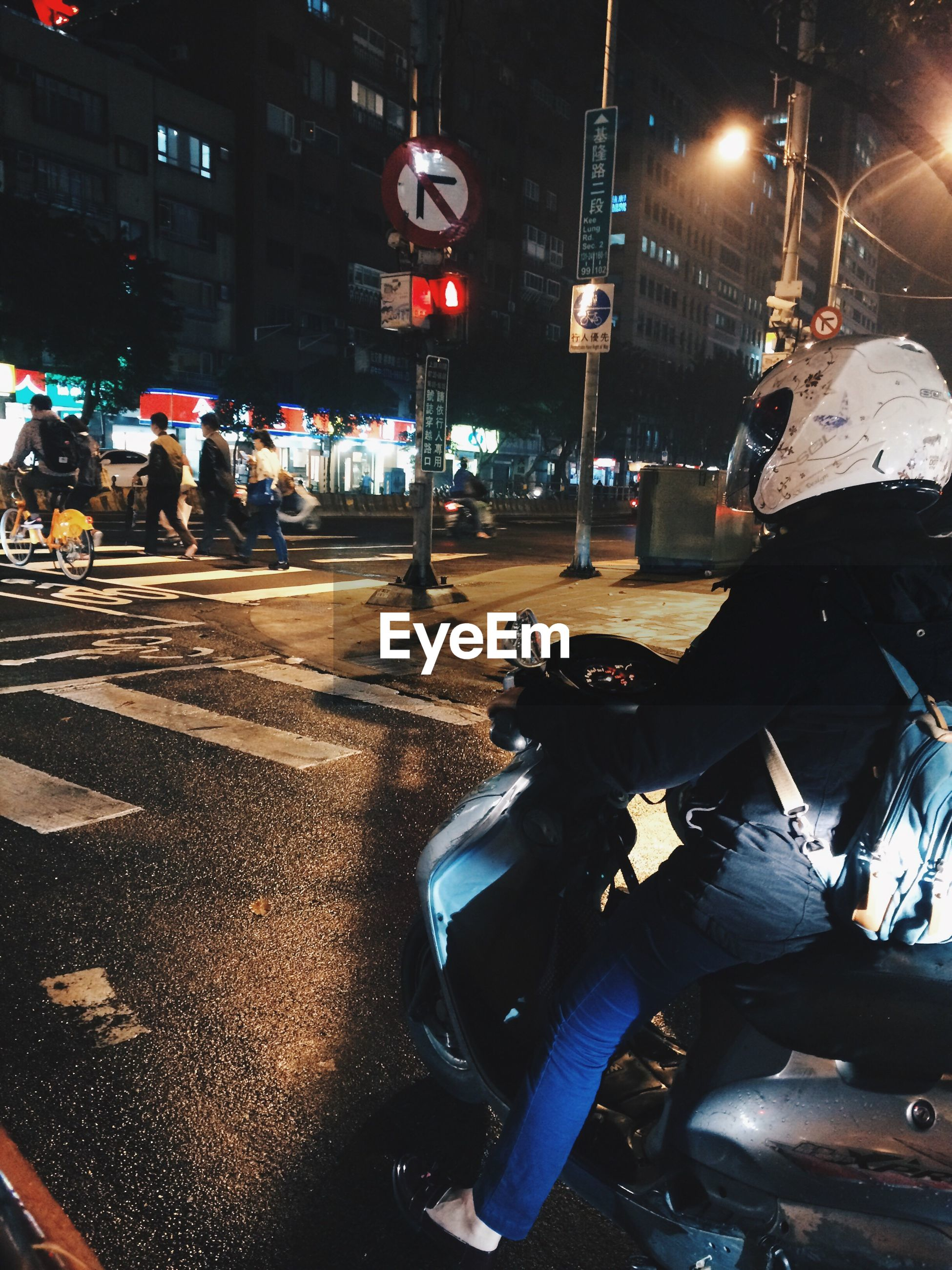 Woman riding motor scooter on city street at night