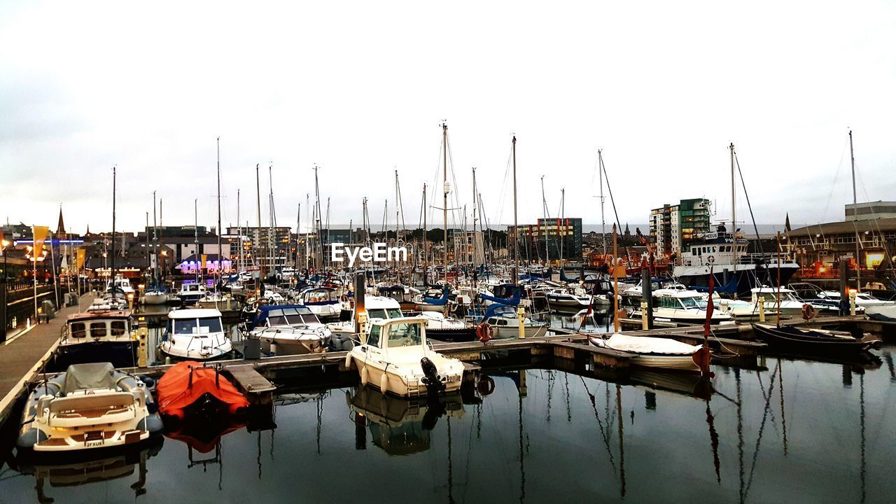 nautical vessel, moored, transportation, water, mode of transportation, harbor, sailboat, pole, mast, reflection, sky, waterfront, nature, no people, day, sea, marina, architecture, built structure, port, yacht